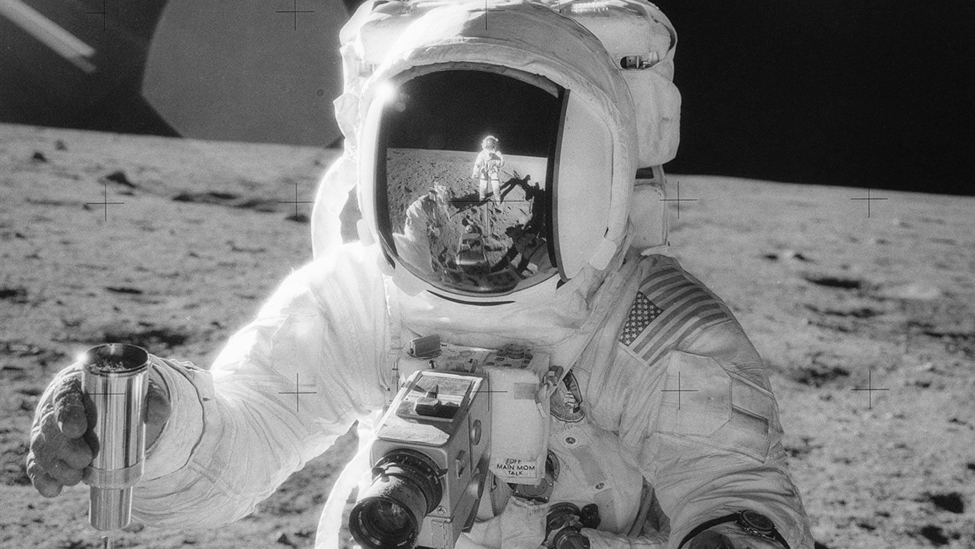 "Apollo 12 lunar module pilot Alan Bean holds a container of lunar soil, with the reflection of mission commander Charles ""Pete"" Conrad Jr. visible on his visor."