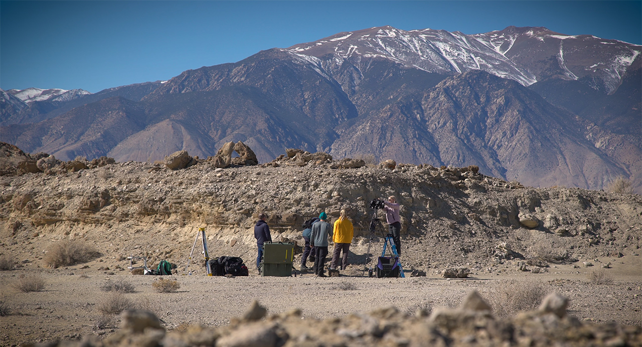 A field team sets up equipment in a dry lakebed in the Nevada
