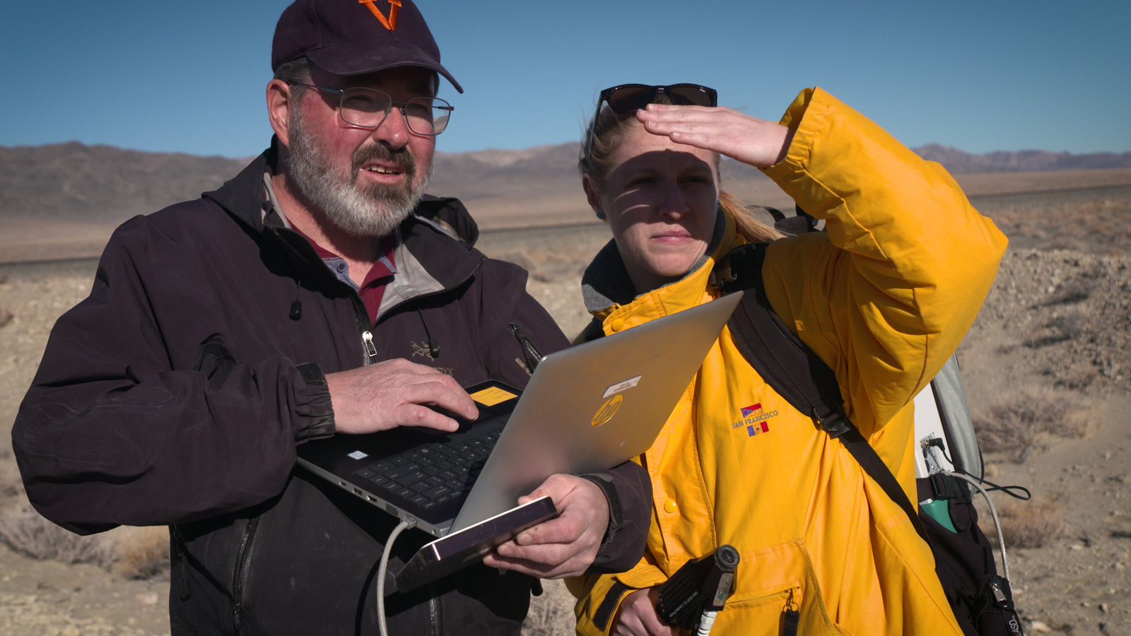 Two JPL scientists in a dry lakebed in the Nevada desert