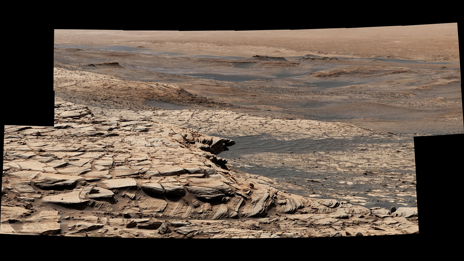 "Curiosity Mars rover captured this view from ""Greenheugh Pediment."" In the foreground is the pediment's sandstone cap. At center is the ""clay-bearing unit""; the floor of Gale Crater is in the distance."