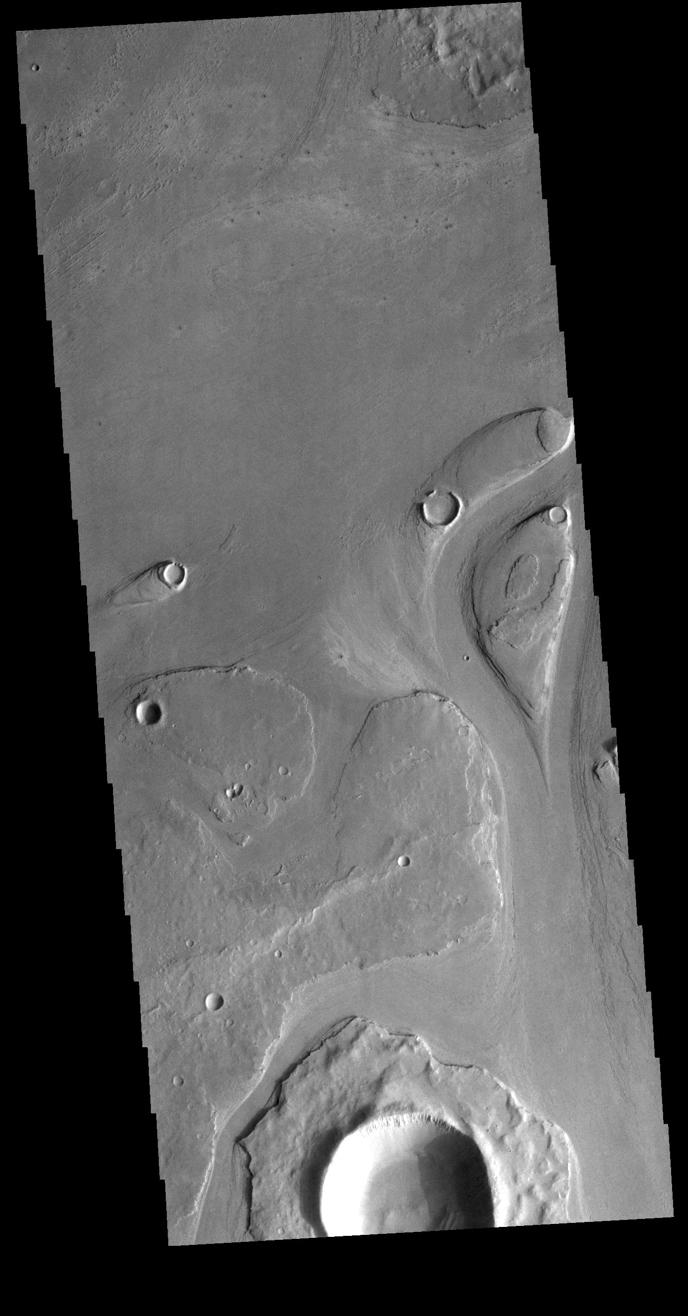 This image from NASAs Mars Odyssey shows part of Athabasca Valles. Several streamlined islands are visible, with tails pointing downstream.