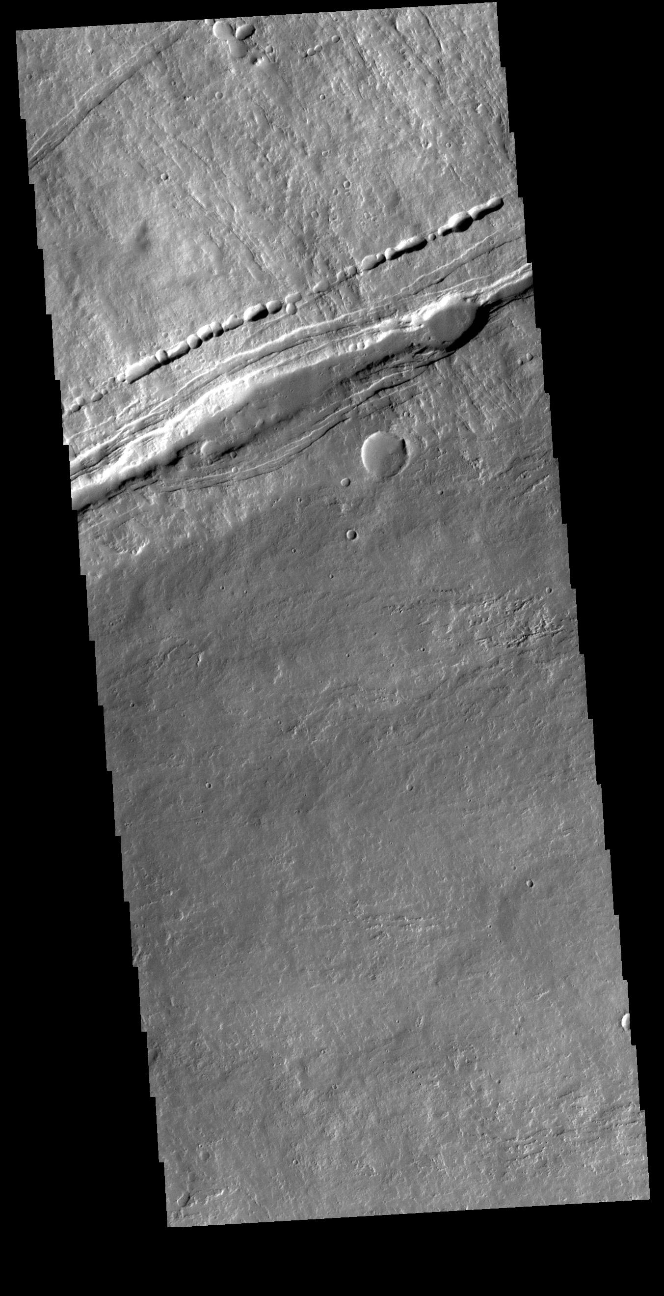 This image from NASAs Mars Odyssey shows the contact of the southern flank of Ascraeus Mons and the surrounding Tharsis region lava flows.