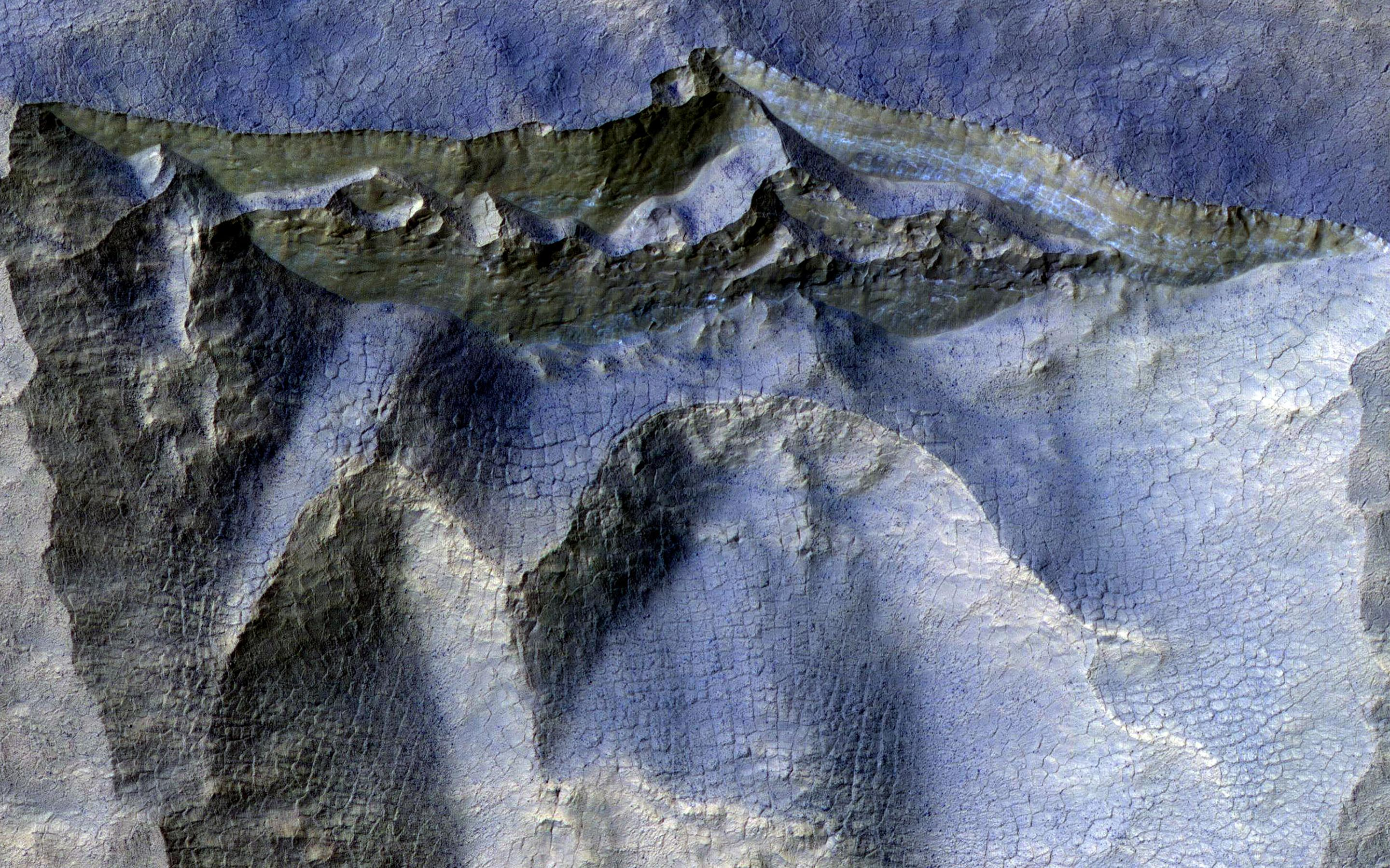 This image acquired on August 15, 2020 by NASAs Mars Reconnaissance Orbiter, shows a brownish, dusty cliff wall, where the faint light-blue-colored ice shows through.