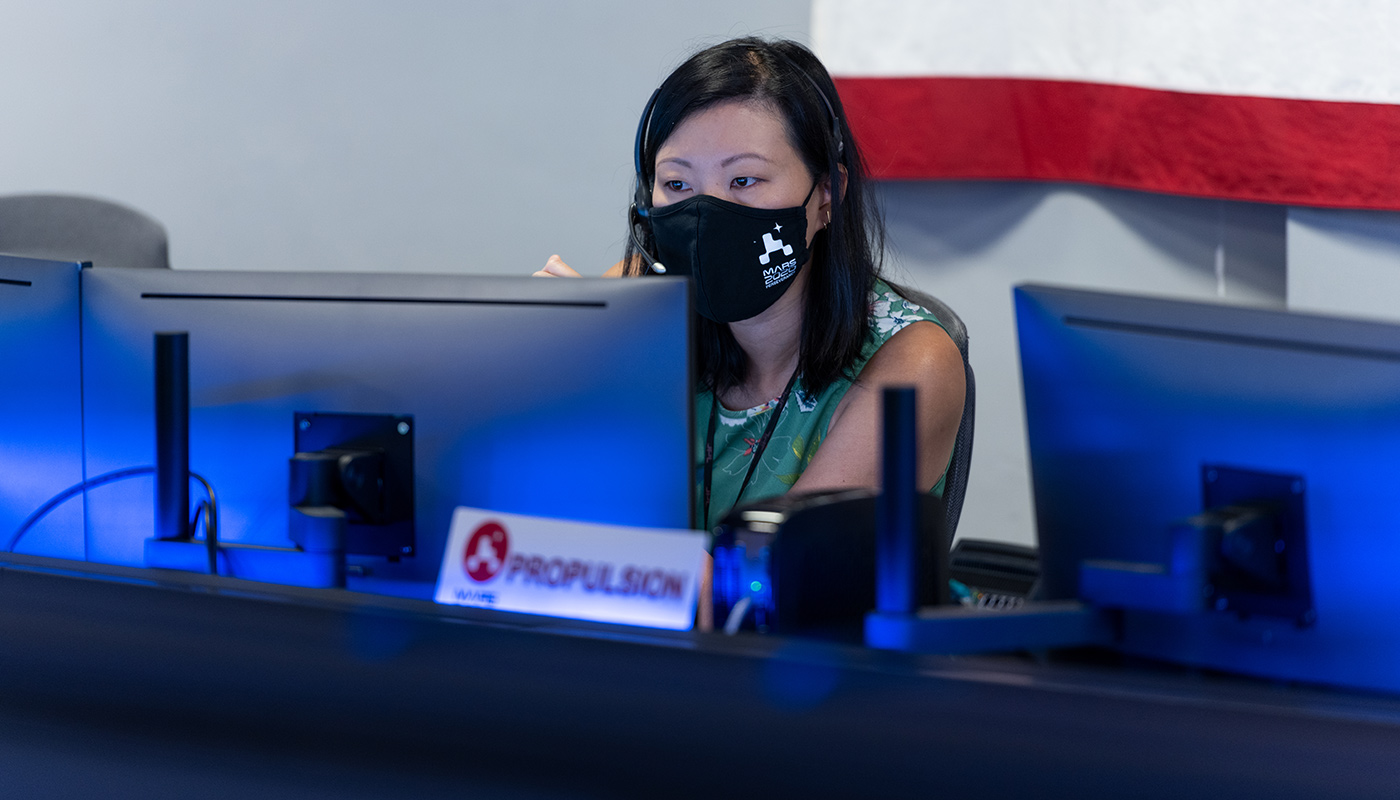 Woman in mask looking at computer in mission control
