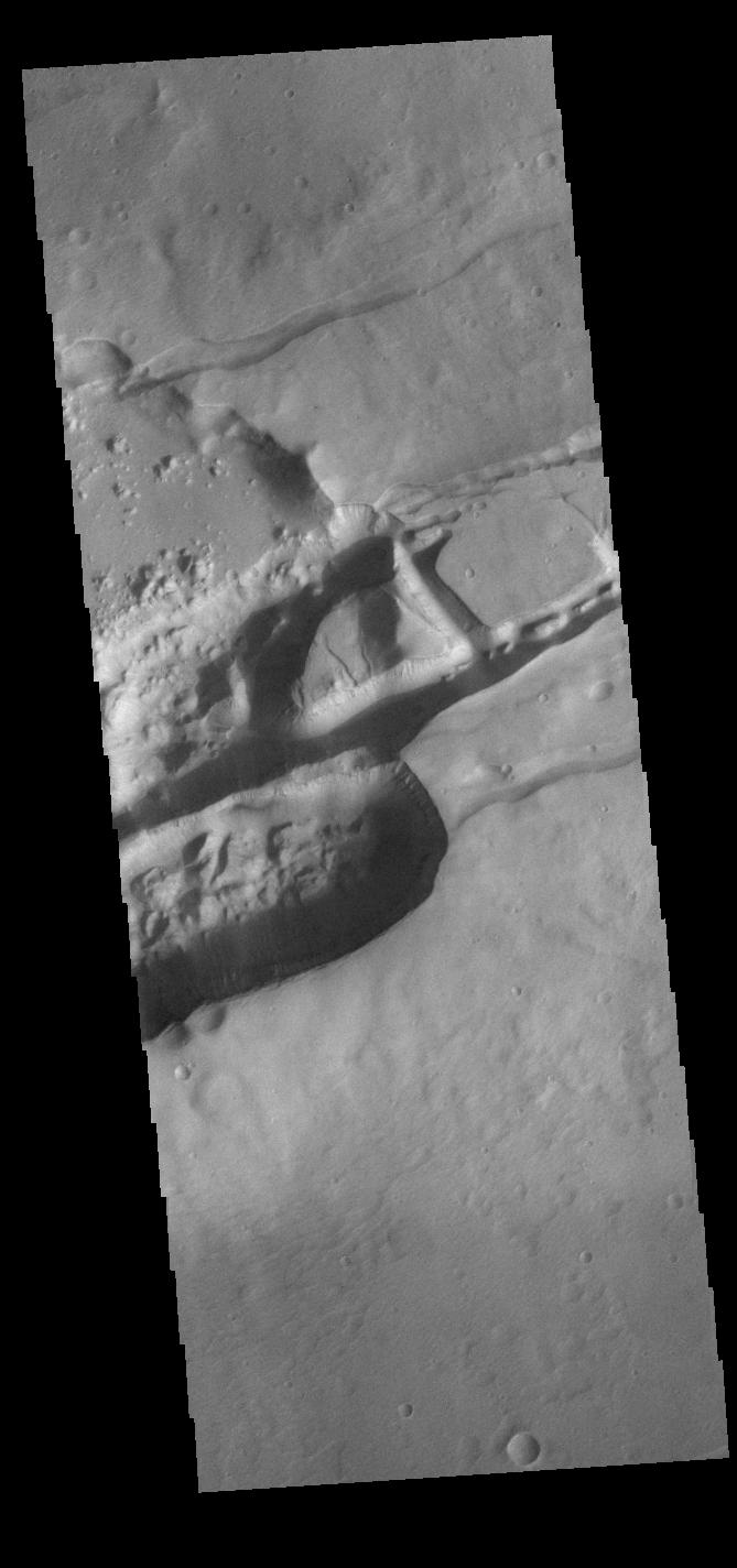 This image from NASAs Mars Odyssey shows linear depressions that are part of Sirenum Fossae.