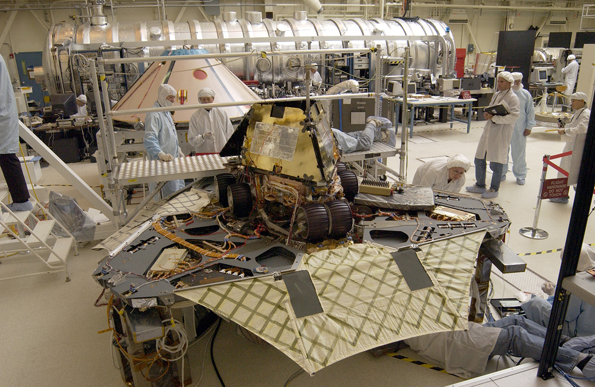 "A ""Martian mechanic"" checks beneath the completely deployed Rover 1 lander. Atop the lander is Rover 1 with its wheels and solar arrays in the stowed position."