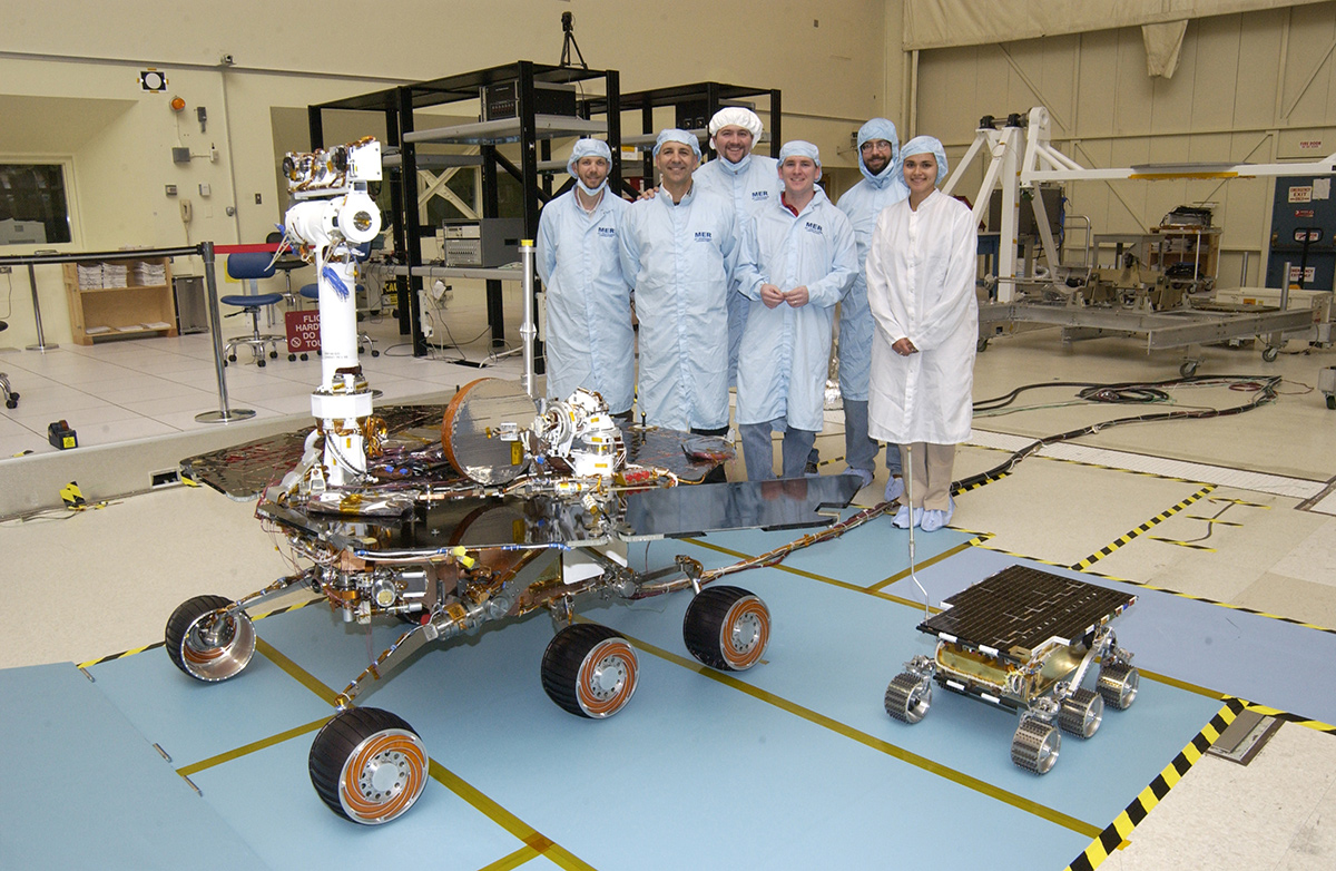 Members of the Mars Exploration Rovers Assembly, Test and Launch Operations team gather around Rover 2 and its predecessor, a flight spare of the Pathfinder mission's Sojourner rover, named Marie Curie.