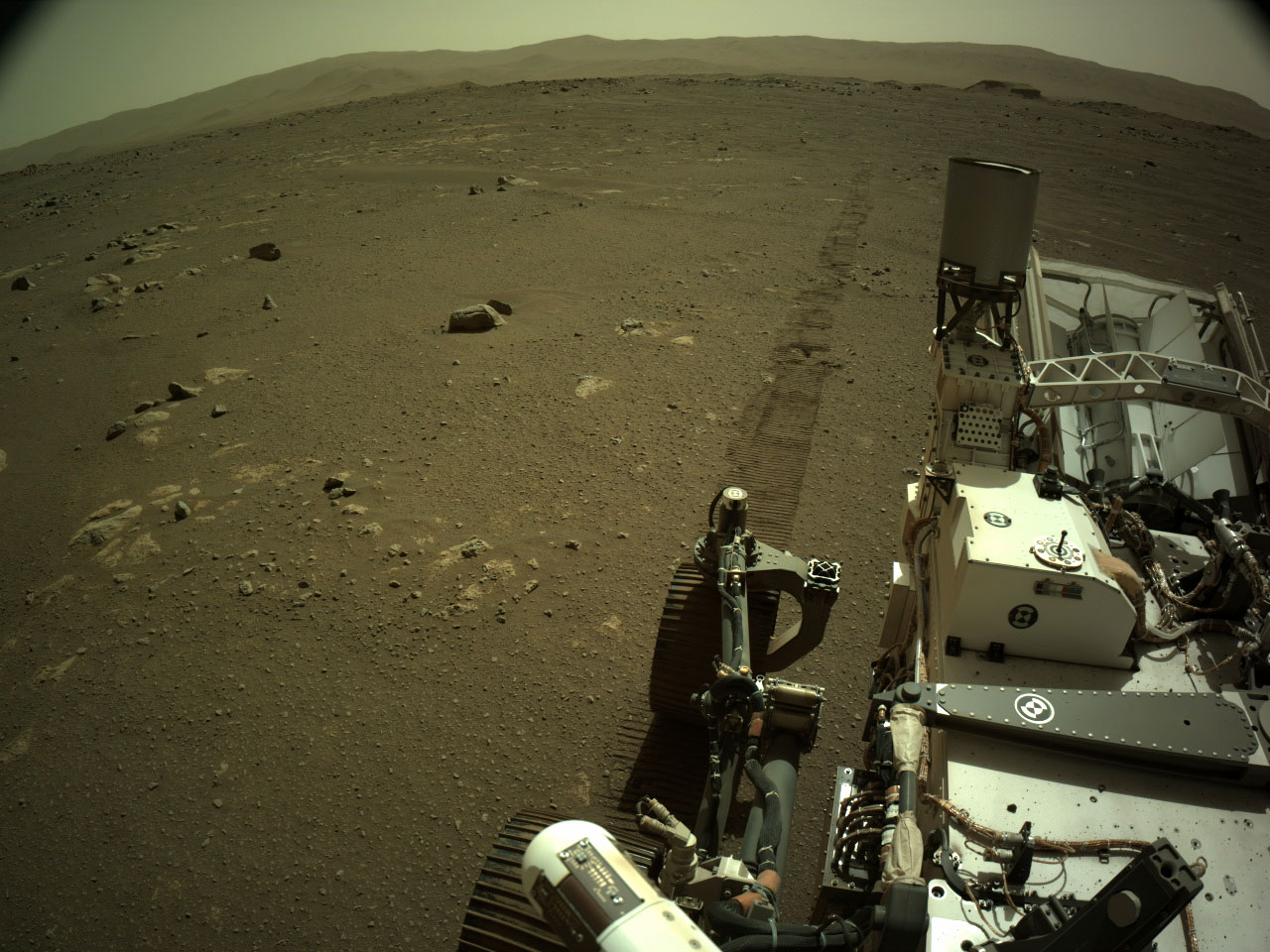 Image taken by Perseverance after driving with rover tracks behind it.