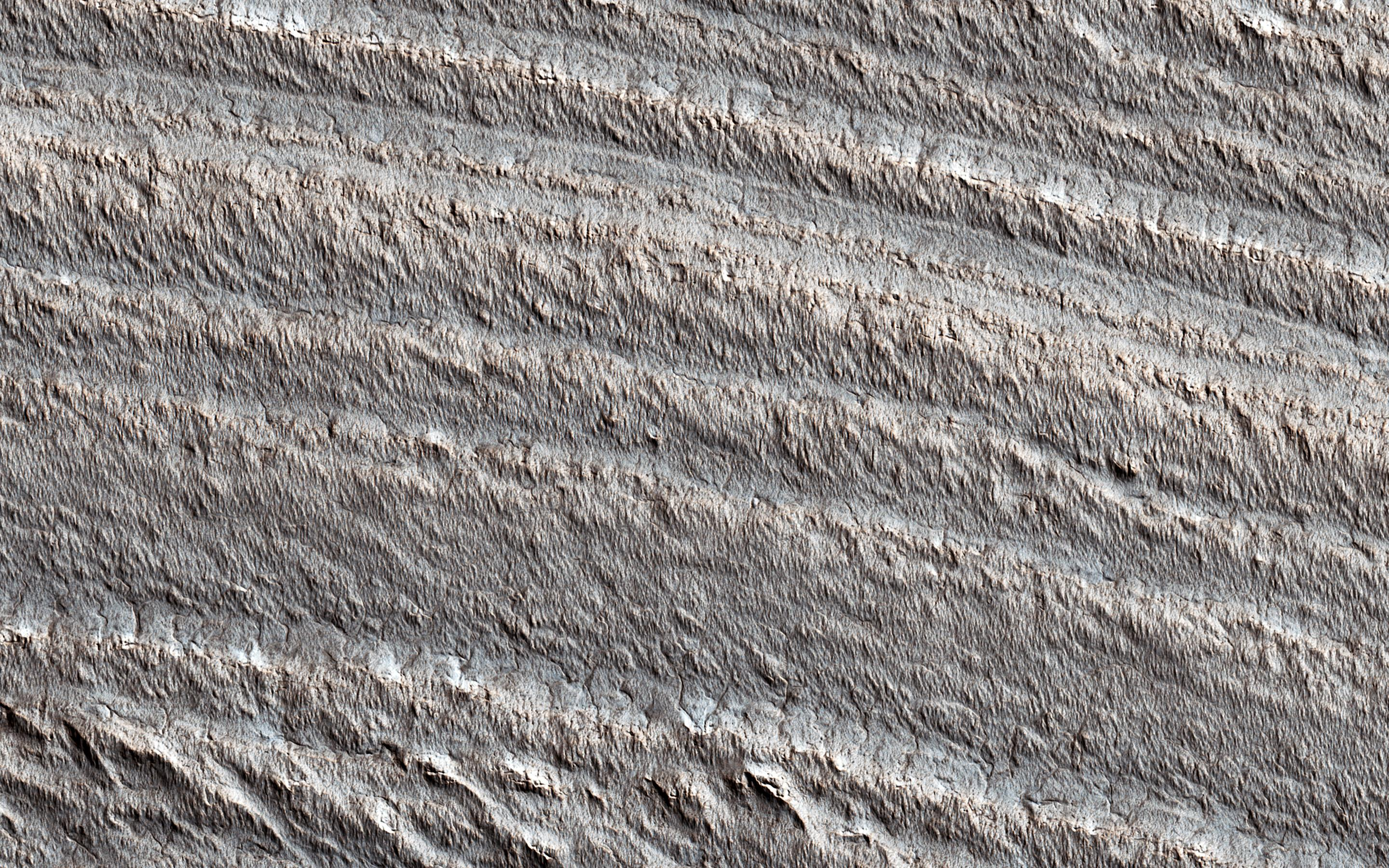This image acquired on October 23, 2020 by NASAs Mars Reconnaissance Orbiter, shows layering near the base of the south polar layered deposits (SPLD). Radar observations of these deposits show that they are rich in water ice.