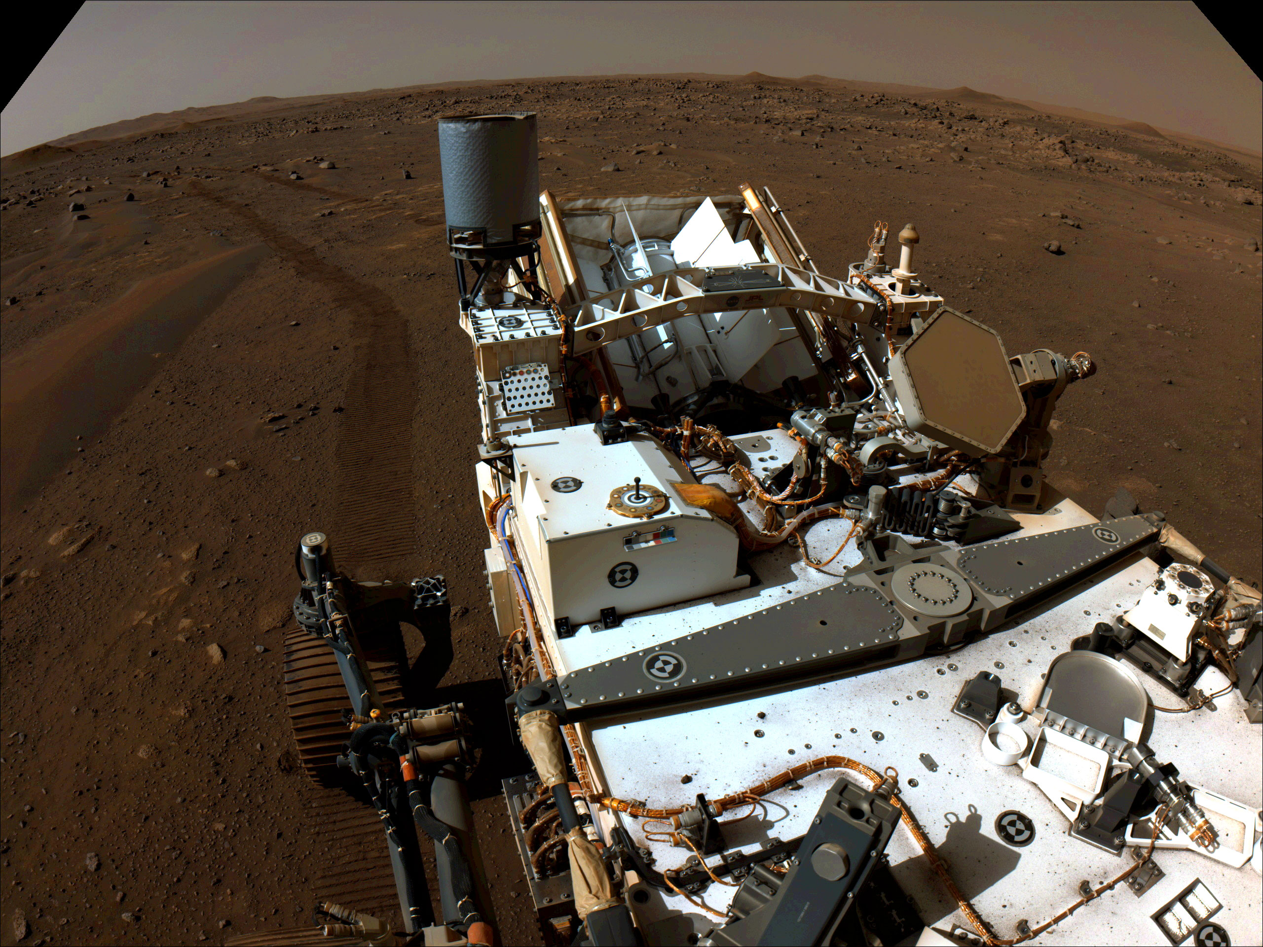 The Perseverance rover can be seen in this image looking back. The rover's tracks are imprinted into the rocky, sandy surface and hills are visible in the background.
