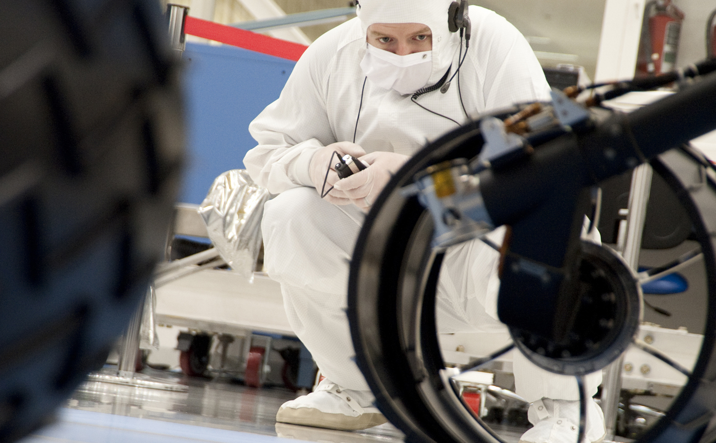 A test operator in clean-room garb observes rolling of the wheels during the first drive test of NASA's Curiosity rover, on July 23, 2010.