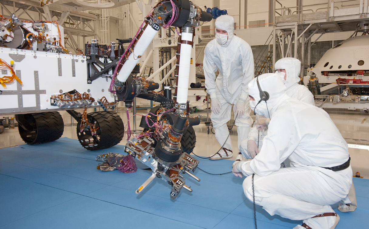 Test operators in a clean room at NASA's Jet Propulsion Laboratory, Pasadena, Calif., monitor some of the first motions by the robotic arm on the Mars rover Curiosity after installation in August 2010. This photo, taken Aug. 31, 2010, shows the arm in a partially extended position. The arm has a reach of about 2.3 meters (7.5 feet) from the front of the rover body.