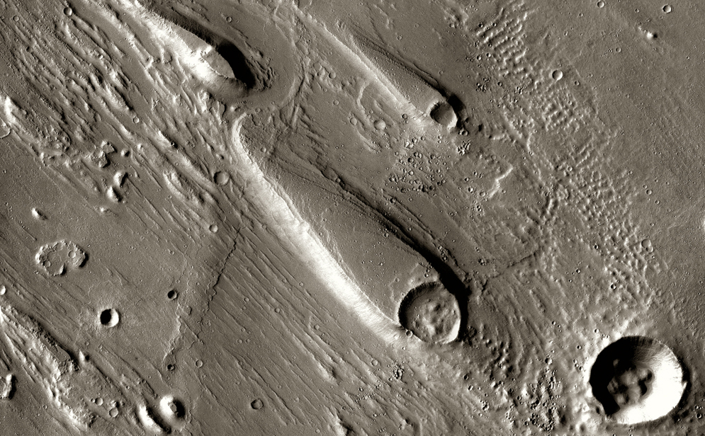 In Ares Vallis, teardrop mesas extend like pennants behind impact craters, where the raised rocky rims diverted the floods and protected the ground from erosion.