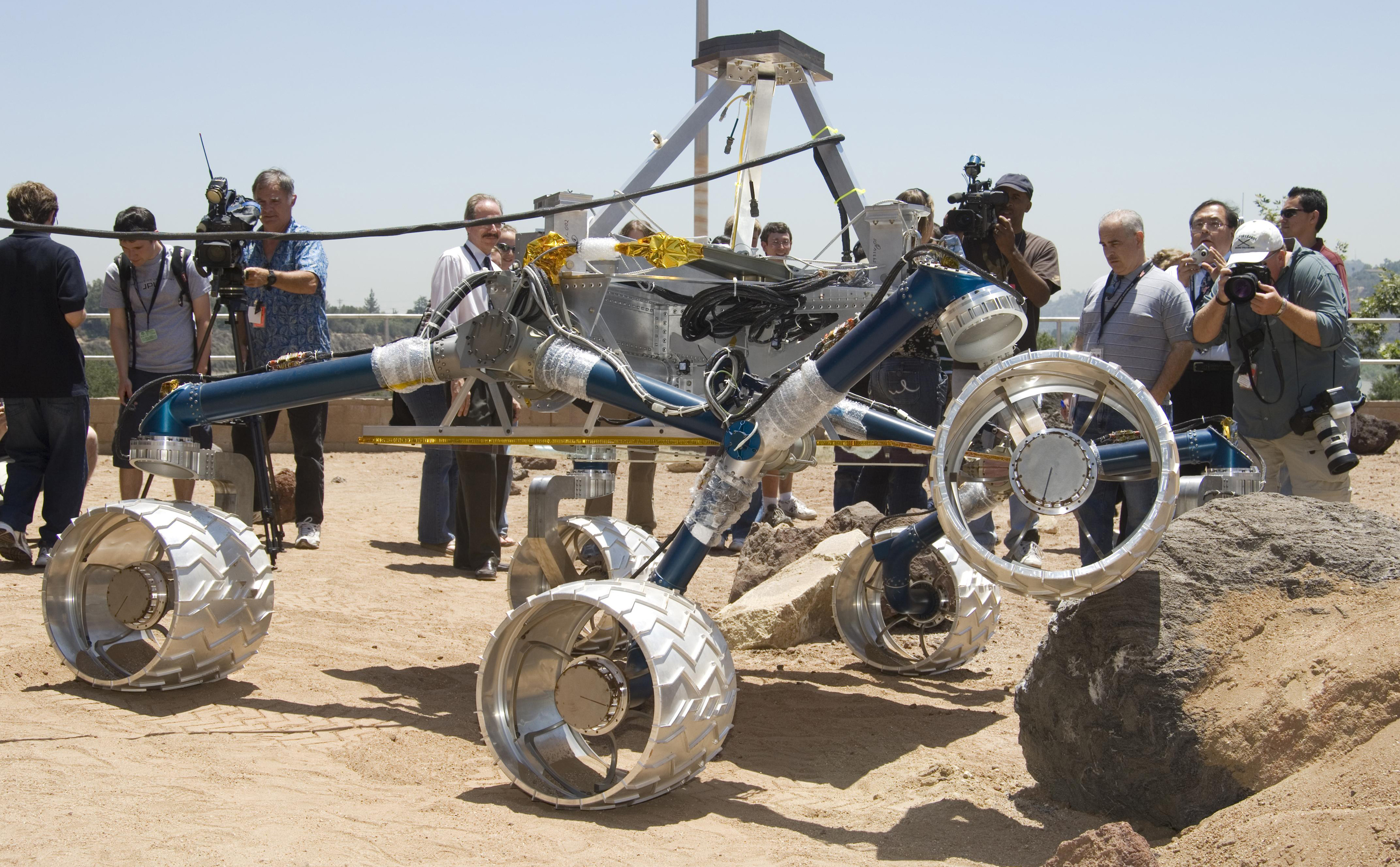 Onlookers watch as Scarecrow, a mobility-testing model for NASA's Mars Science Laboratory, easily conquers boulders in the Mars Yard testing area at NASA's Jet Propulsion Laboratory.