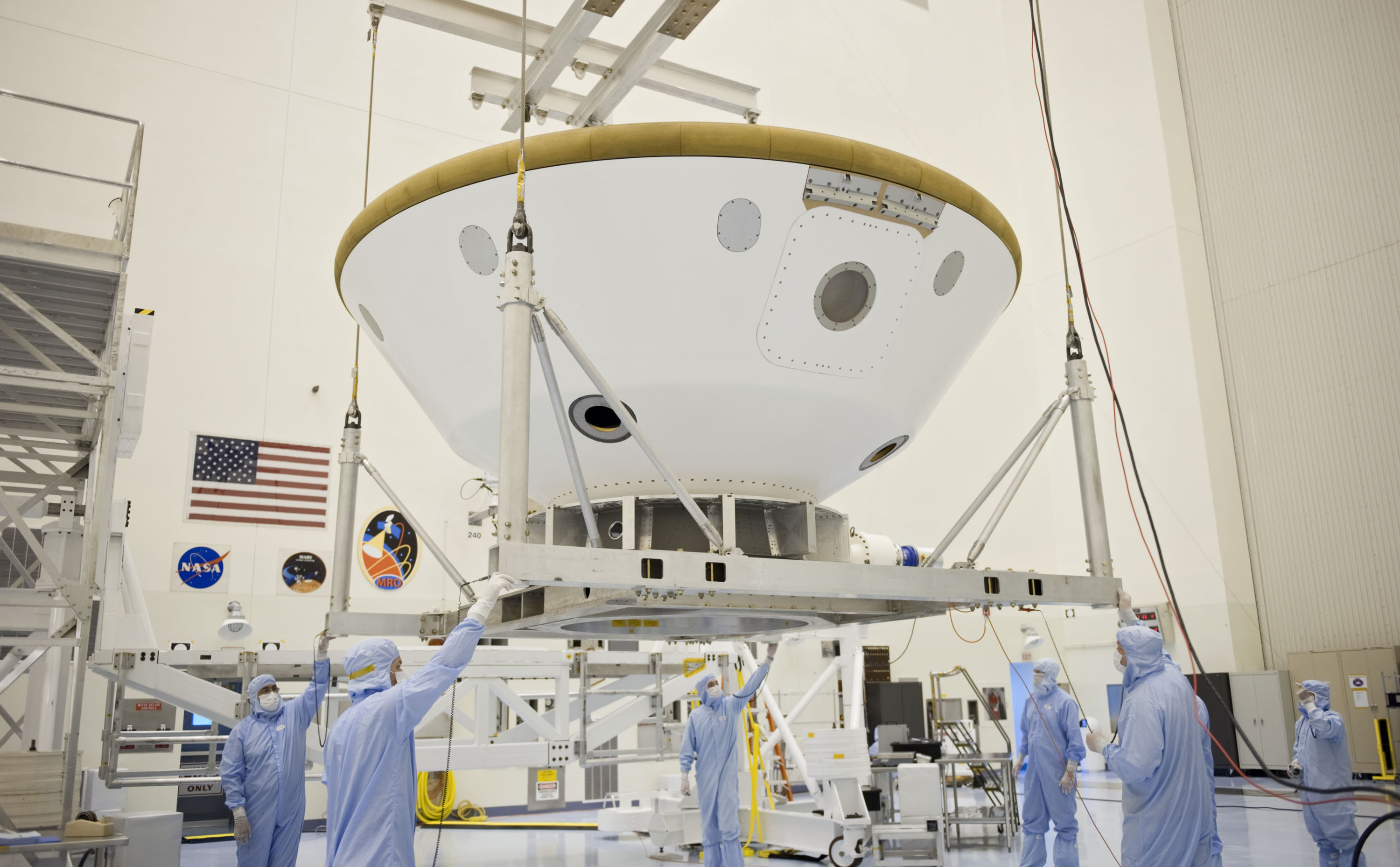 At the Payload Hazardous Servicing Facility at NASA's Kennedy Space Center in Florida, technicians using an overhead crane, move the aeroshell, a component of NASA's Mars Science Laboratory (MSL), back to a work stand after a spin and balance test.