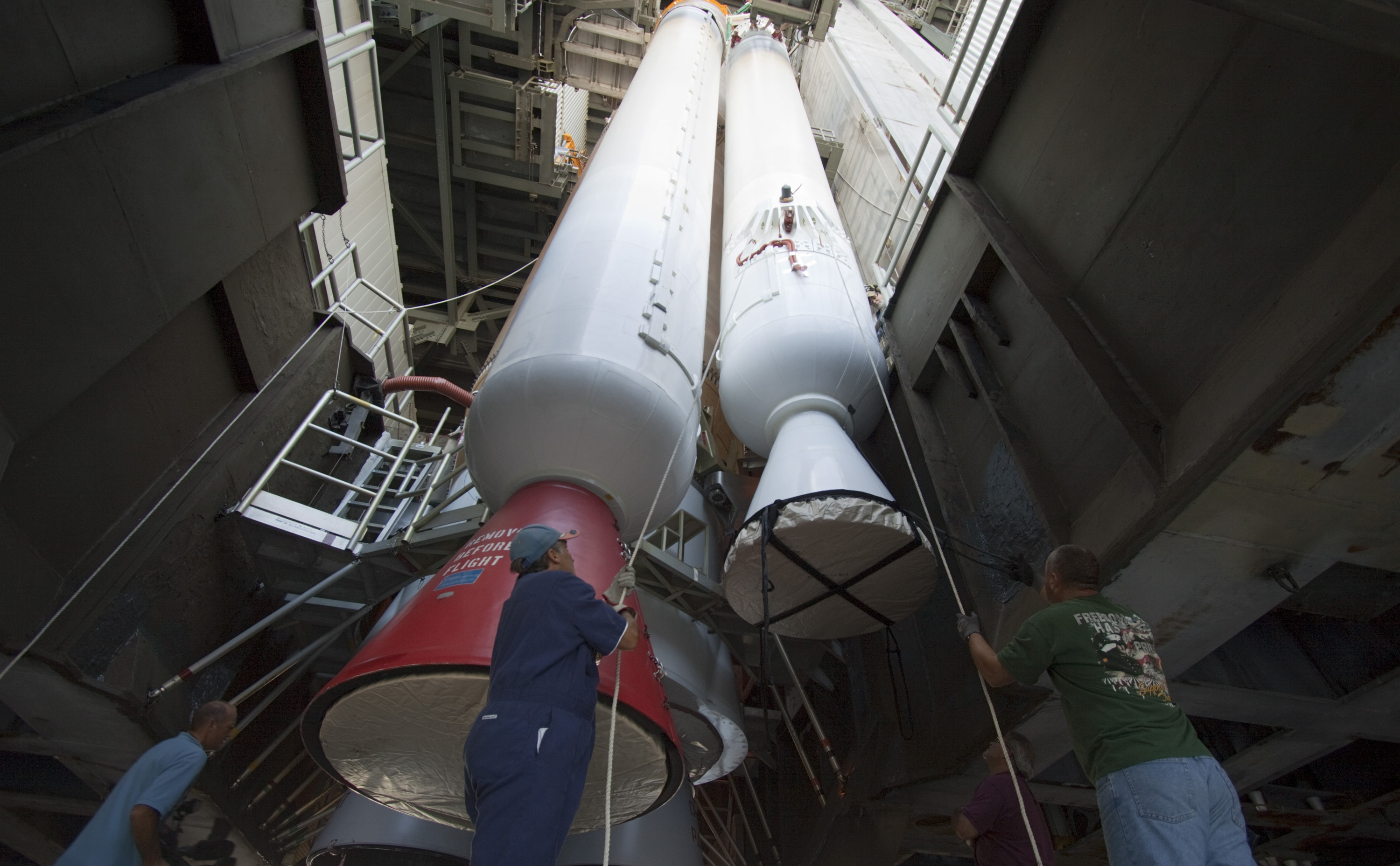 Inside the Vertical Integration Facility at Space Launch Complex 41 on Cape Canaveral Air Force Station in Florida, technicians using an overhead crane guide the final solid rocket motor into position for mating to the first stage of a United Launch Alliance Atlas V rocket.