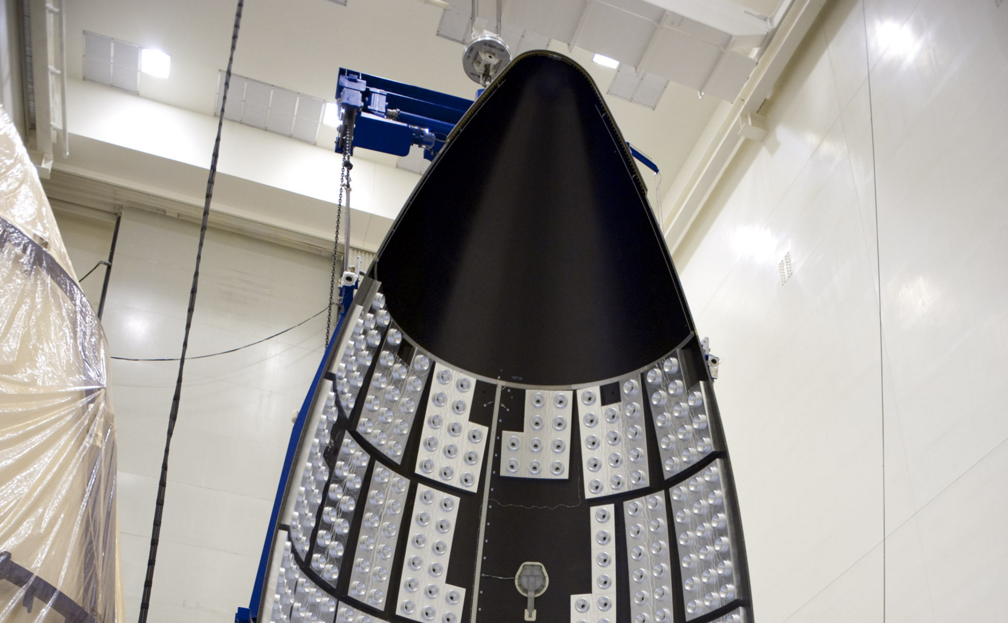 In the Payload Hazardous Servicing Facility at NASA's Kennedy Space Center in Florida, a section of the Atlas V payload fairing for NASA's Mars Science Laboratory (MSL) mission hangs vertically from the ceiling.