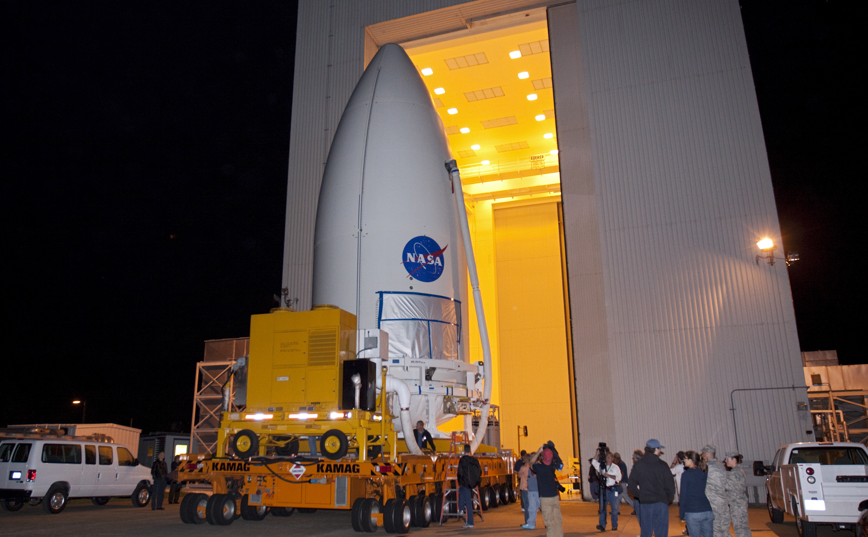 Standing atop a payload transporter, the Atlas V rocket payload fairing containing NASA's Mars Science Laboratory (MSL) spacecraft rolls out of the Payload Hazardous Servicing Facility at Kennedy Space Center in Florida, beginning the move to Space Launch Complex 41.