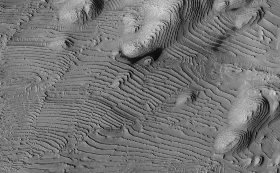 Rhythmic patterns of sedimentary layering in Danielson Crater on Mars result from periodic changes in climate related to changes in tilt of the planet.