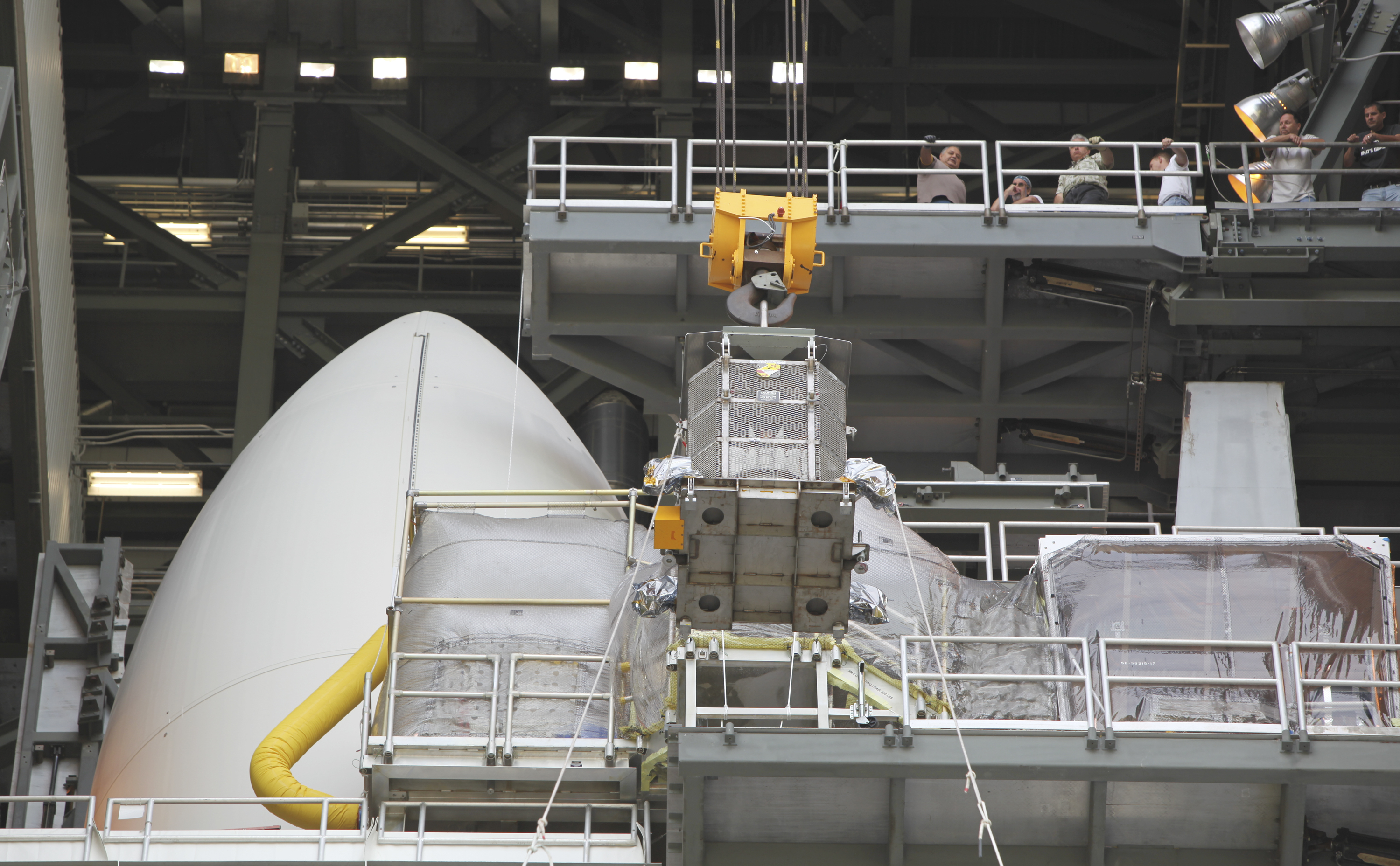 "Employees gathered one level above monitor the progress of the protective mesh container known as the ""gorilla cage,"" holding the multi-mission radioisotope thermoelectric generator (MMRTG) for NASA's Mars Science Laboratory (MSL) mission, as it is lifted near the top of the Atlas V rocket in the Vertical Integration Facility at Space Launch Complex 41."