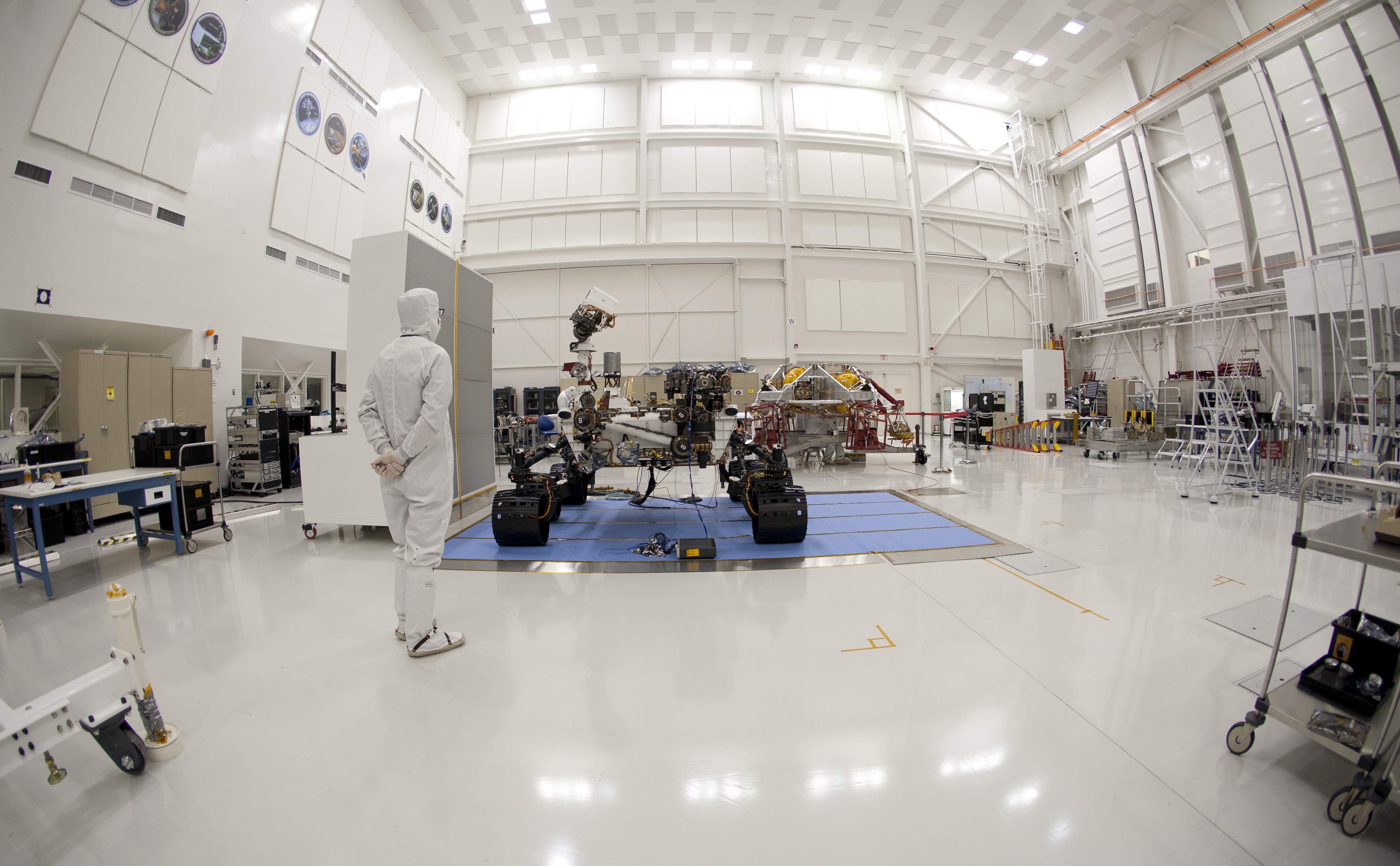 An engineer says goodbye to the Curiosity rover and its powered descent vehicle in the Jet Propulsion Laboratory's Spacecraft Assembly Facility shortly before the spacecraft was readied for shipment to Kennedy Space Center for launch.