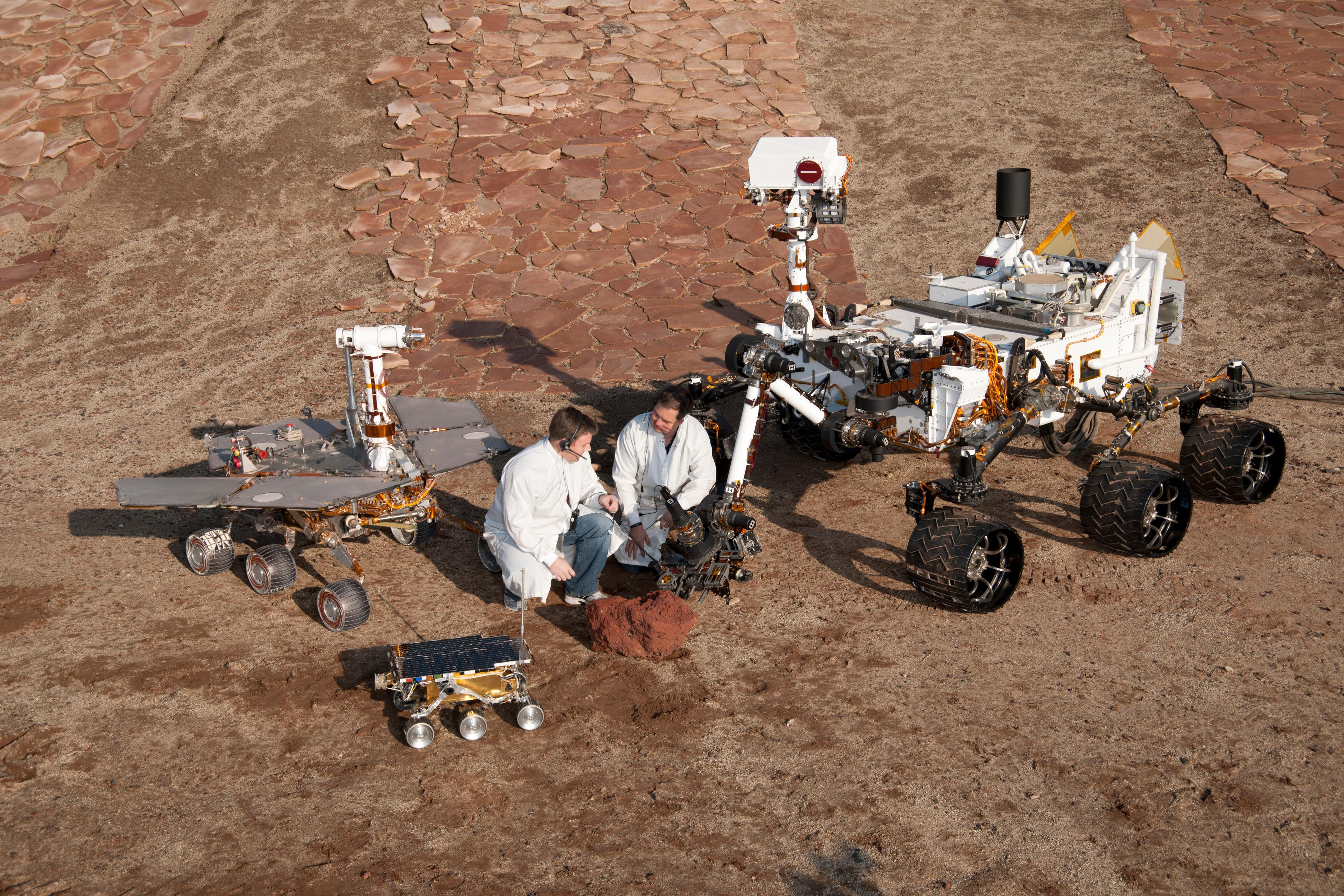 Two spacecraft engineers join a grouping of vehicles providing a comparison of three generations of Mars rovers developed at NASA's Jet Propulsion Laboratory, Pasadena, Calif. The setting is JPL's Mars Yard testing area.