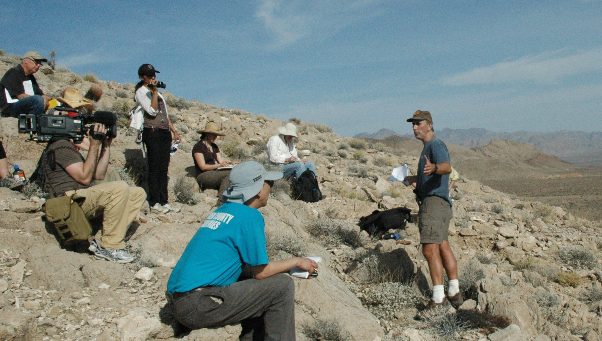 A group of journalists take part in a field trip to learn about the clues hidden in the rock layers with Curiosity Project Scientist, John Grotzinger.