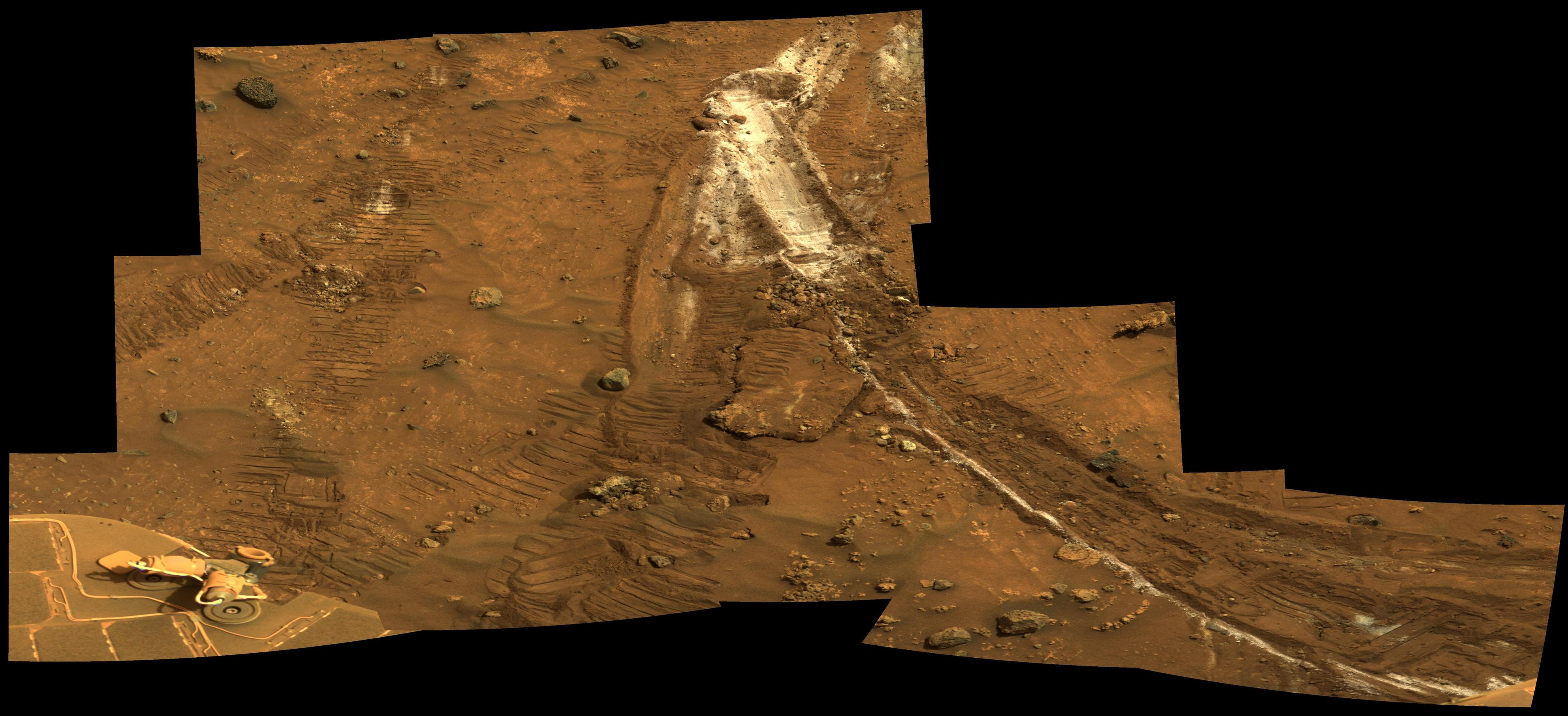 tracks on Mars with a patch of white soil showing