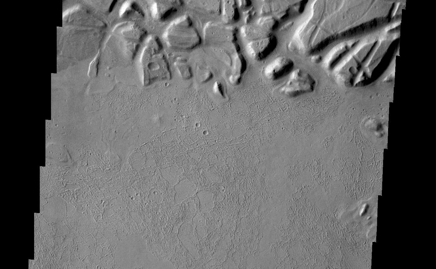 Echus Chasma forms the boundary between the Tharsis volcanoes to the west and Lunae Planum to the east. This region is one of both tectonically fractured rocks (top of image) and volcanic flows (middle and bottom of image). Echus Chasma empties into Kasei Valles.