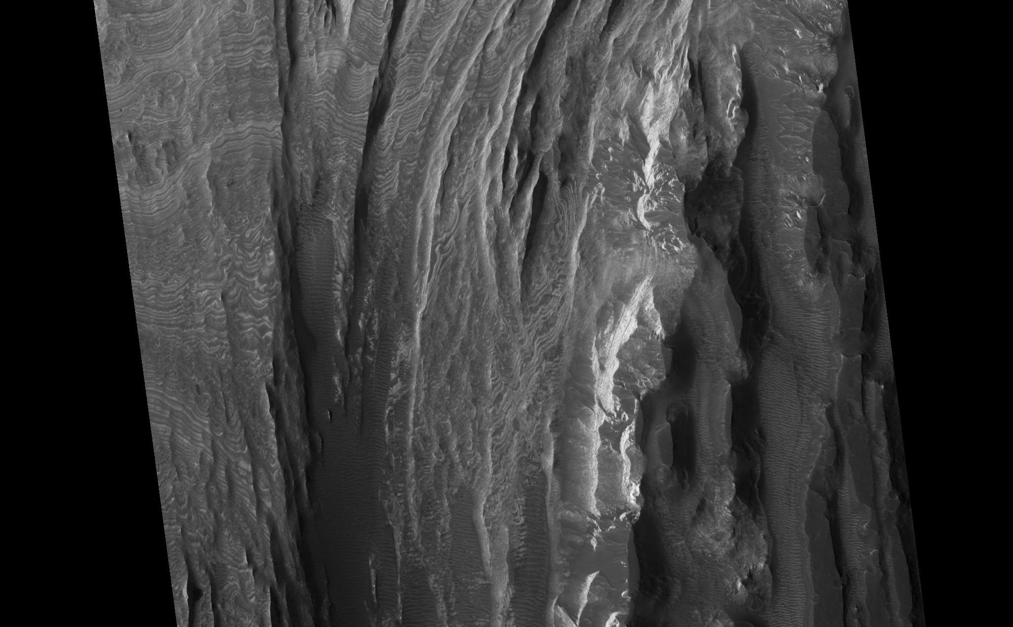 This HiRISE image shows a portion of interior layered deposits (ILD) in Juventae Chasma. Juventae Chasma is a large depression near the equatorial canyon system Valles Marineris. The scene is along the top of a mound of layered deposits on the floor of Juventae Chasma. Dunes are seen in the low-lying, darker regions. Very fine layers are also seen (see subimage, approximately 1 km across). Understanding what kinds of materials formed the layers, how they were set in place, and how they have evolved will provide insight into Martian geologic history.