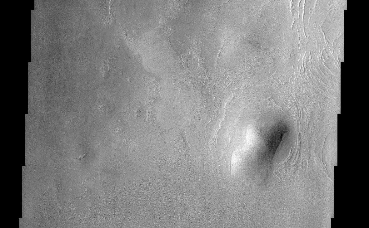 "This THEMIS image of rounded hills and ridges in Arcadia Planitia shows a very intriguing geomorphic feature that may be attributed to the presence of an icy-rock mixture of material. Smooth aprons of material are observed to be preferentially located on the cold, north facing slopes of hills and extend further and beyond the deposits located on other sides. These smooth deposits are in stark contrast to the more rough surfaces that dominate the scene and it has been suggested that they represent a preserved mixture of ice and rock. How exactly this deposit forms still remains a mystery. They may have been ""pasted"" onto the slopes and preserved on the cold facing sides or they may represent the result of downslope motion of material that is enhanced by the presence of ground ice. In either case, this interesting observation suggests that ground ice may still play an important role in the formation and preservation of martian surface features."