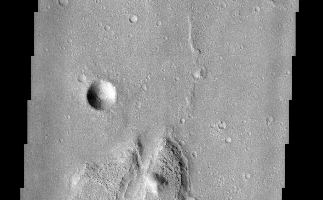 This lunar-like scene occurs along the southeastern rim of the Isidis Planitia basin. The Isidis basin is an ancient impact crater some 1200 km across that is found along the boundary separating the heavily-cratered southern highland terrain of Mars from the northern lowlands. Elements of both terrains are evident in this image as an island of rugged highland terrain surrounded by smoother lowland terrain. The resurfacing of the Isidis basin produced a system of wrinkle ridges, some of which are seen on the lowland terrain in the image. Wrinkle ridges are a common feature on the surface of the moon and add to the lunar-like quality of this image. Layers are visible in the large island, the most resistant of which likely are from lava flows that created the highland terrain. The process by which the global-scale highland/lowland dichotomy was created remains a mystery.