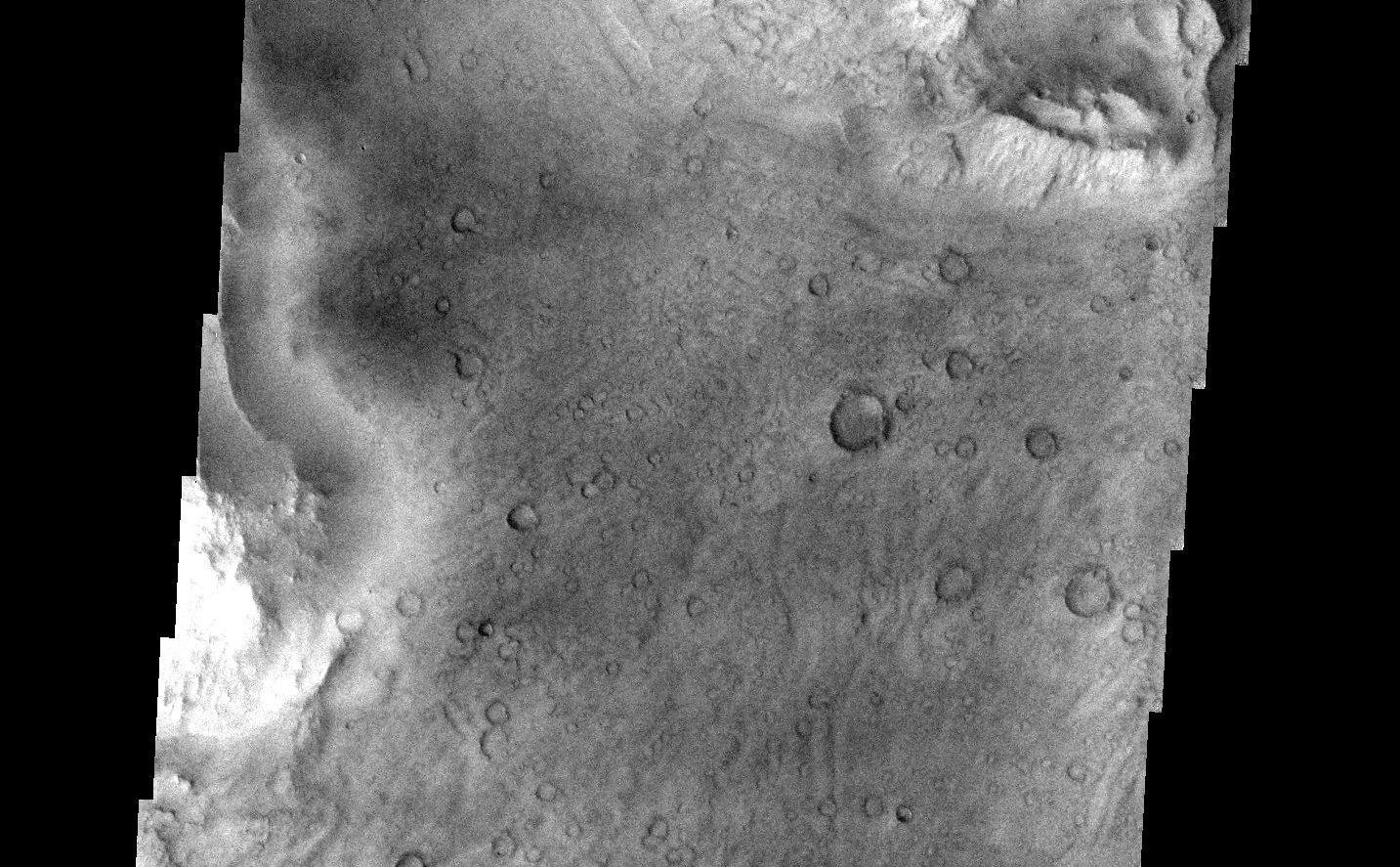 This image is located near the boundary between Syrtis Major and Isidis Planitia. The top of the image shows rough material that has eroded away from the lower portion of the image, revealing an underlying surface that has many small craters. It also reveals an ancient flow lobe that is barely discernable, crossing the southern part of the image (this flow lobe is much easier to see as a smooth region in the context image).
