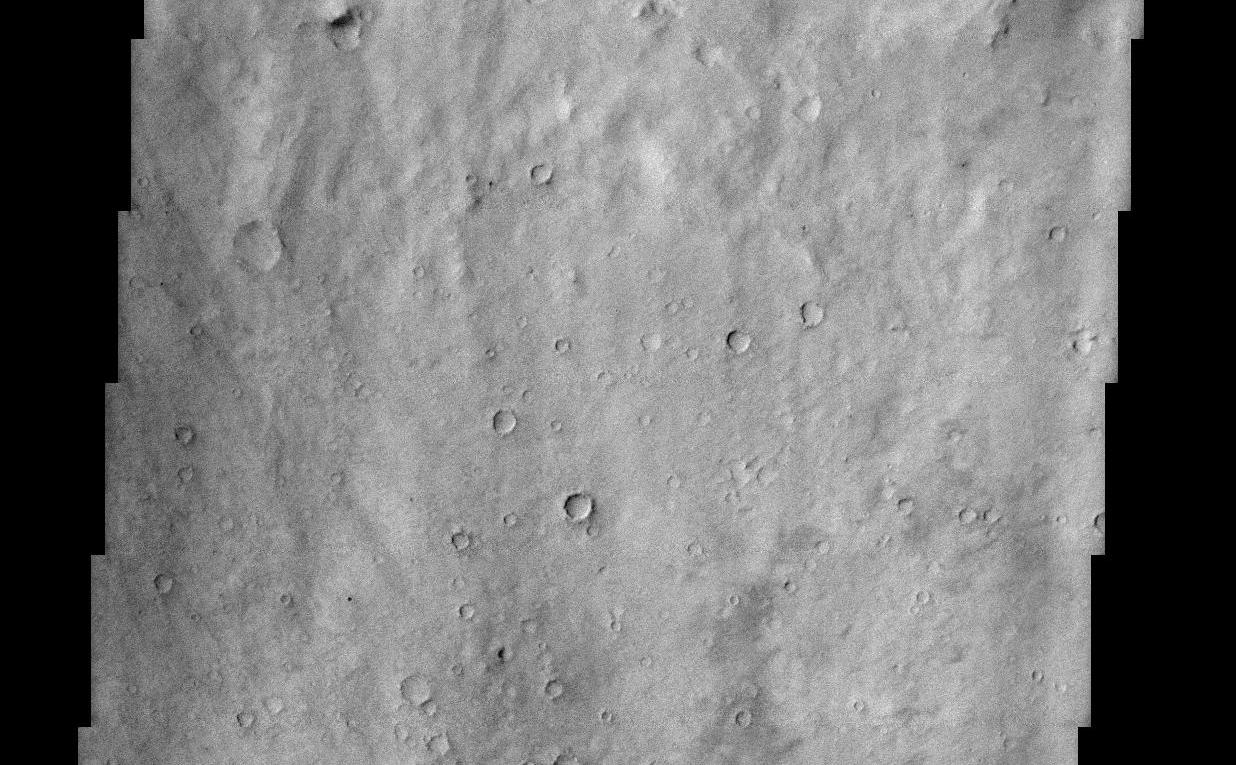 "This THEMIS visible image shows a close-up view of the ridged plains in Hesperia Planum. This region is the classic locality for martian surfaces that formed in the ""middle ages"" of martian history. The absolute age of these surfaces is not well known. However, using the abundance of impact craters, it is possible to determine that the Hesperian plains are younger than the ancient cratered terrains that dominate the southern hemisphere, and are older than low-lying plains of the northern hemisphere. In this image it is possible to see that this surface has a large number of 1-3 km diameter craters, indicating that this region is indeed very old and has subjected to a long period of bombardment. A large (80 km diameter) crater occurs just to the north (above) this image. The material that was thrown out onto the surface when the crater was formed (""crater ejecta"") can be seen at the top of the THEMIS image. This ejecta material has been heavily eroded and modified since its formation, but there are hints of lobate flow features within the ejecta. Lobate ejecta deposits are thought to indicate that ice was present beneath the surface when the crater was formed, leading to these unusual lobate features. Many of the Hesperian plains are characterized by ridged surfaces. These ridges can be easily seen in the MOLA context image, and several can be seen cutting across the lower portion of the THEMIS image. These ""wrinkle"" ridges are thought to be the result of compression (squeezing) of the lavas that form these plains."