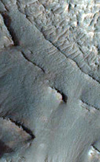 This image shows part of the floor of an impact crater on the northern rim of the giant Hellas Basin.   Hellas includes the lowest elevations on Mars, and may have once held lakes or seas; layered rock outcrops occur around much of the edge of the basin. At this site, a large impact crater (about 90 kilometers across) was partly filled by layered rocks. These rocks on the crater floor are now eroding and forming strange pits.  Here, the layers are mostly exposed on a steep slope which cuts across much of the image. On this slope, they crop out as rocky stripes, some continuous and others not. The material between the stripes is mostly covered by debris, but some areas of exposed rock are visible. The slope is capped by a thick, continuous layer that armors it against erosion; once this cap is gone, the lower material is removed rapidly, forming the steep slope. At the base of this slope, rocks on the floor of the pit appear bright and heavily fragmented by cracks known as joints.  The variation in rock types suggests that the rocks here were deposited by multiple processes or in different environments. Sites like this may preserve a record of conditions on early Mars.