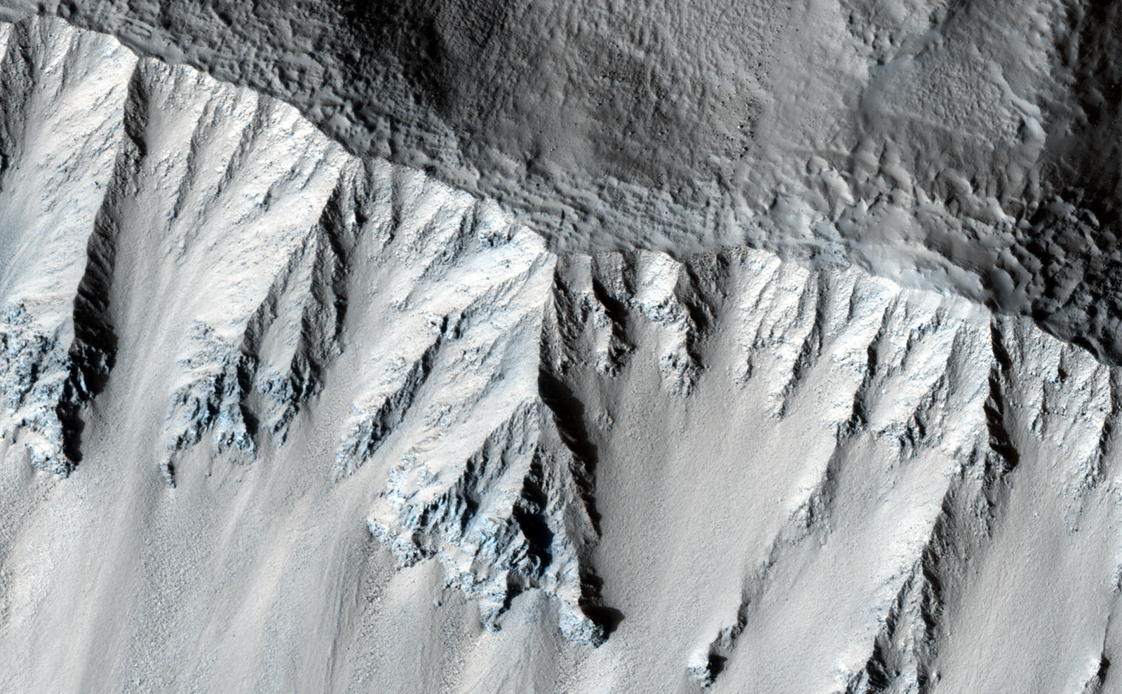 This fresh crater is located in the northern mid-latitudes. It is designated as fresh because of its very sharp rim.  The crater has experienced some modification since it formed, including a few tiny craters on the south wall.  The rough texture of the floor is suggestive of ground ice, which is expected to exist in the mid-latitudes. Ground ice aids gravity in moving material from the crater walls towards the center. Material is visible slumping off the northwest crater wall in this fashion. The wavy texture of the center of the crater floor suggests that material has been transported from the walls and merged in the center.