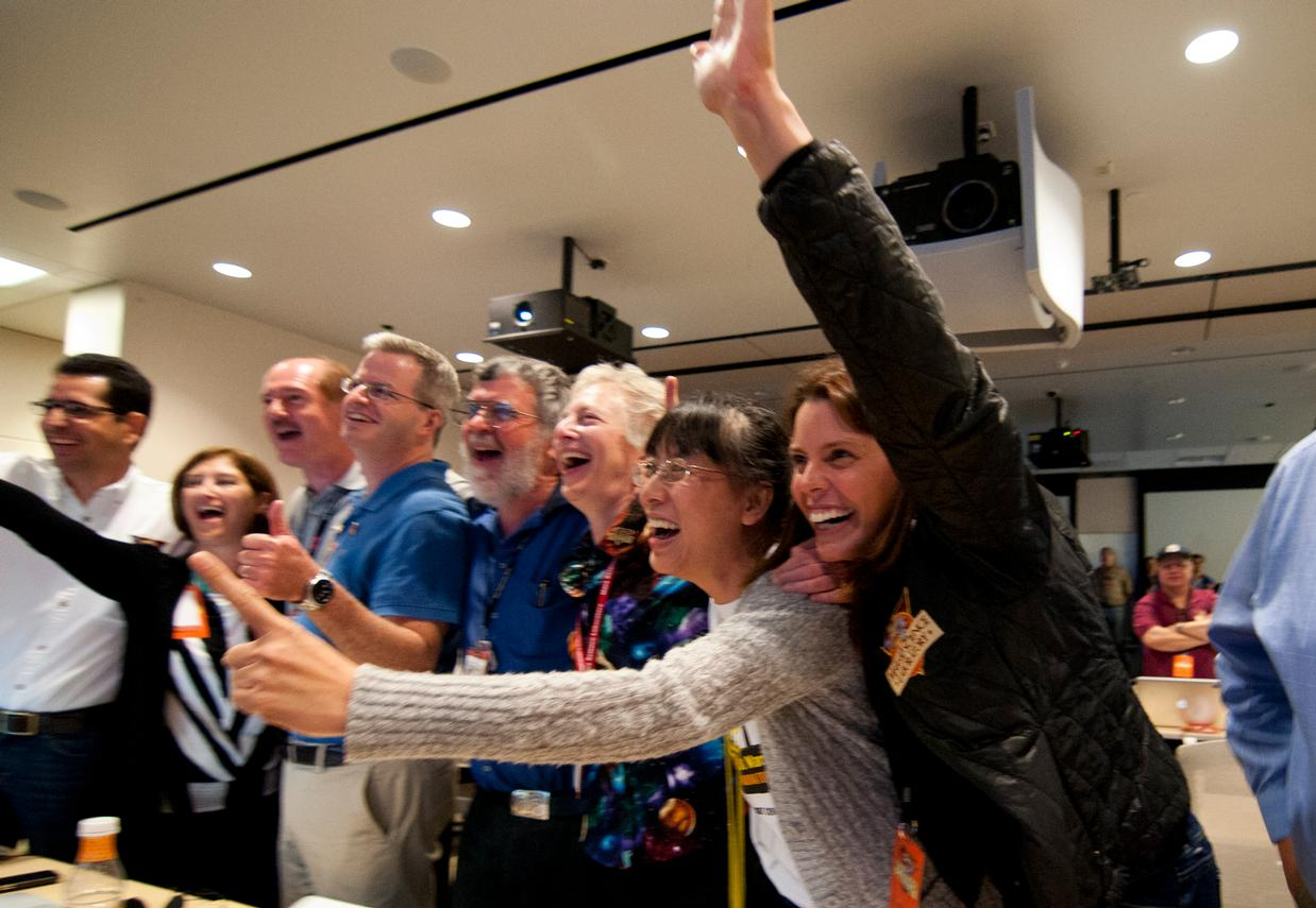 Members of the Curiosity science team jump out of their seats and cheer when they hear that the Curiosity rover has successfully landed on the Martian surface.