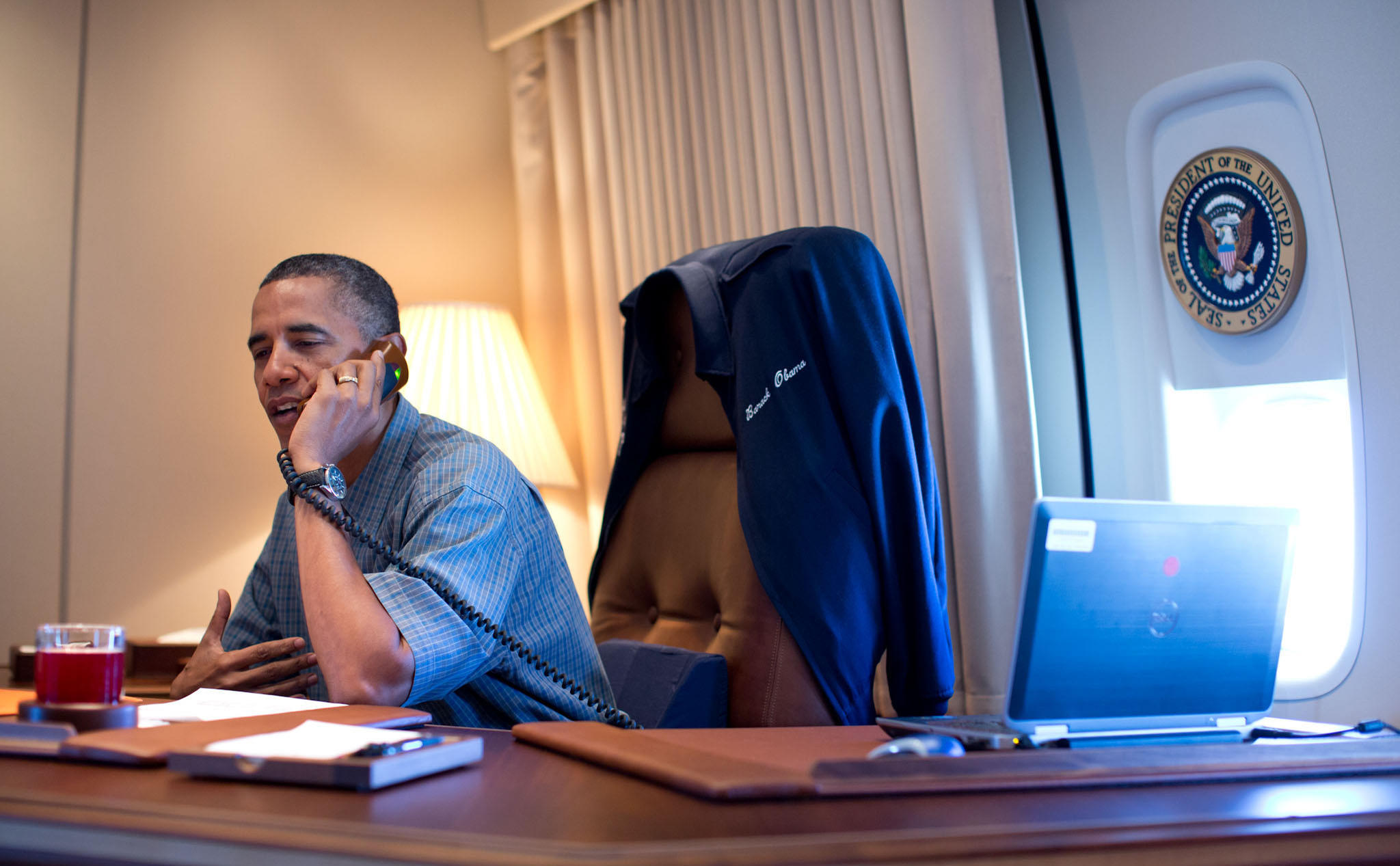 President Barack Obama talks on the phone with NASA's Curiosity Mars rover team aboard Air Force One during a flight to Offutt Air Force Base in Nebraska, Aug. 13, 2012.