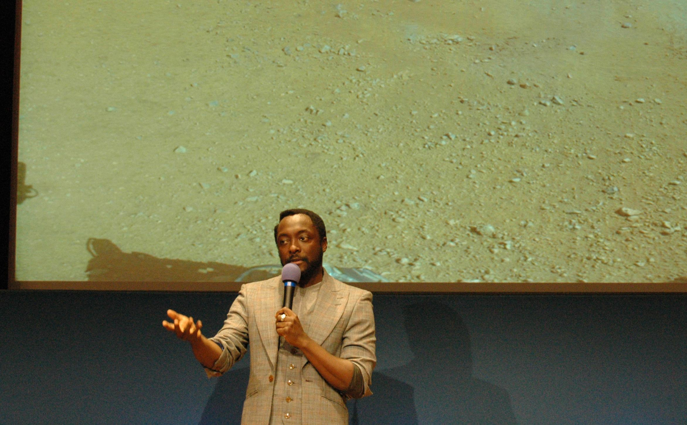 Musician will.i.am addresses a crowd of students at JPL during an event celebrating the first time in history that a recorded song has been beamed back to Earth from another planet.