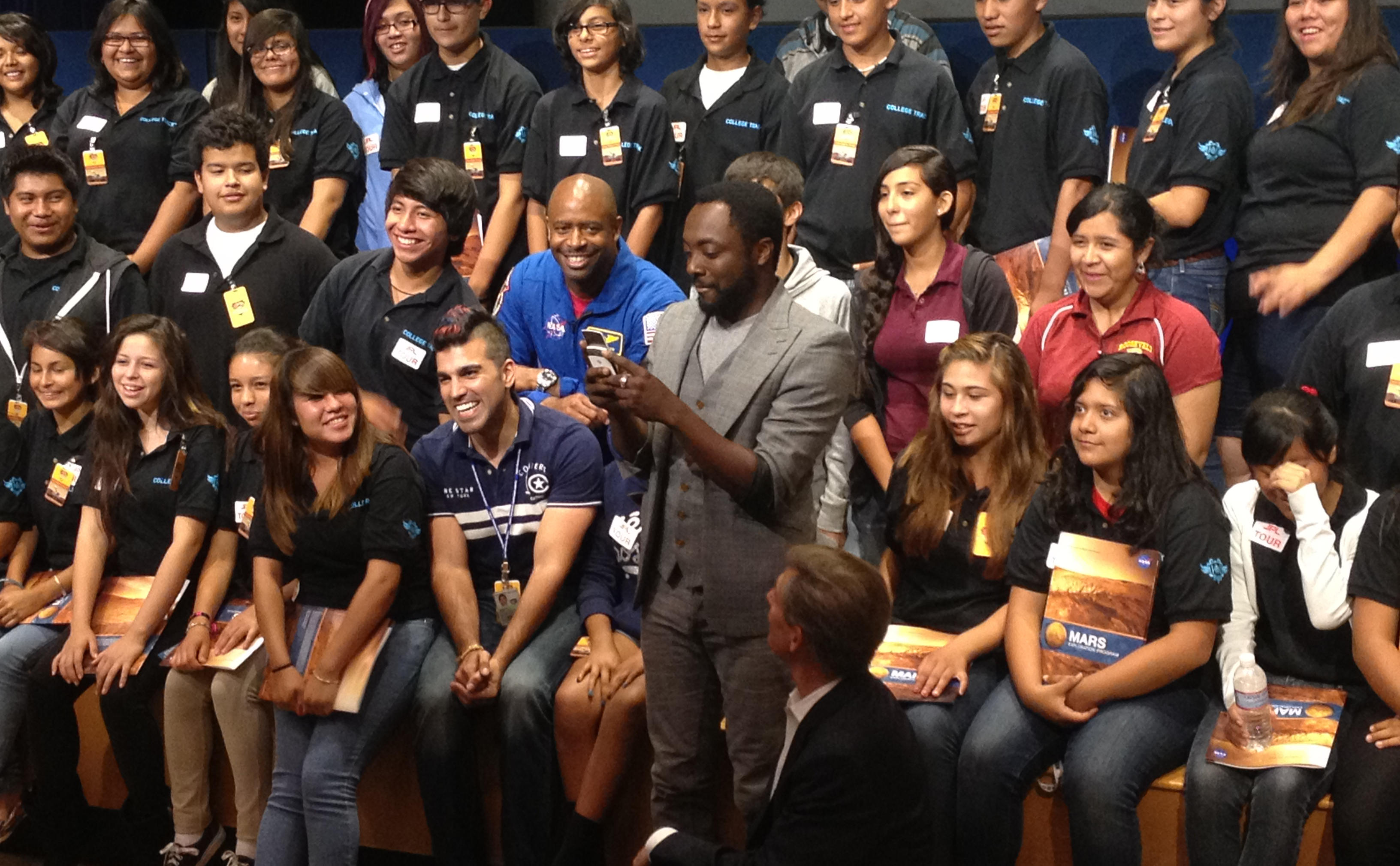 "With students and NASA space shuttle astronaut Leland Melvin looking on, musical artist will.i.am posts a tweet soon after his song ""Reach for the Stars"" was beamed back from the Curiosity Mars rover and broadcast to a live audience at NASA's Jet Propulsion Laboratory in Pasadena, Calif."