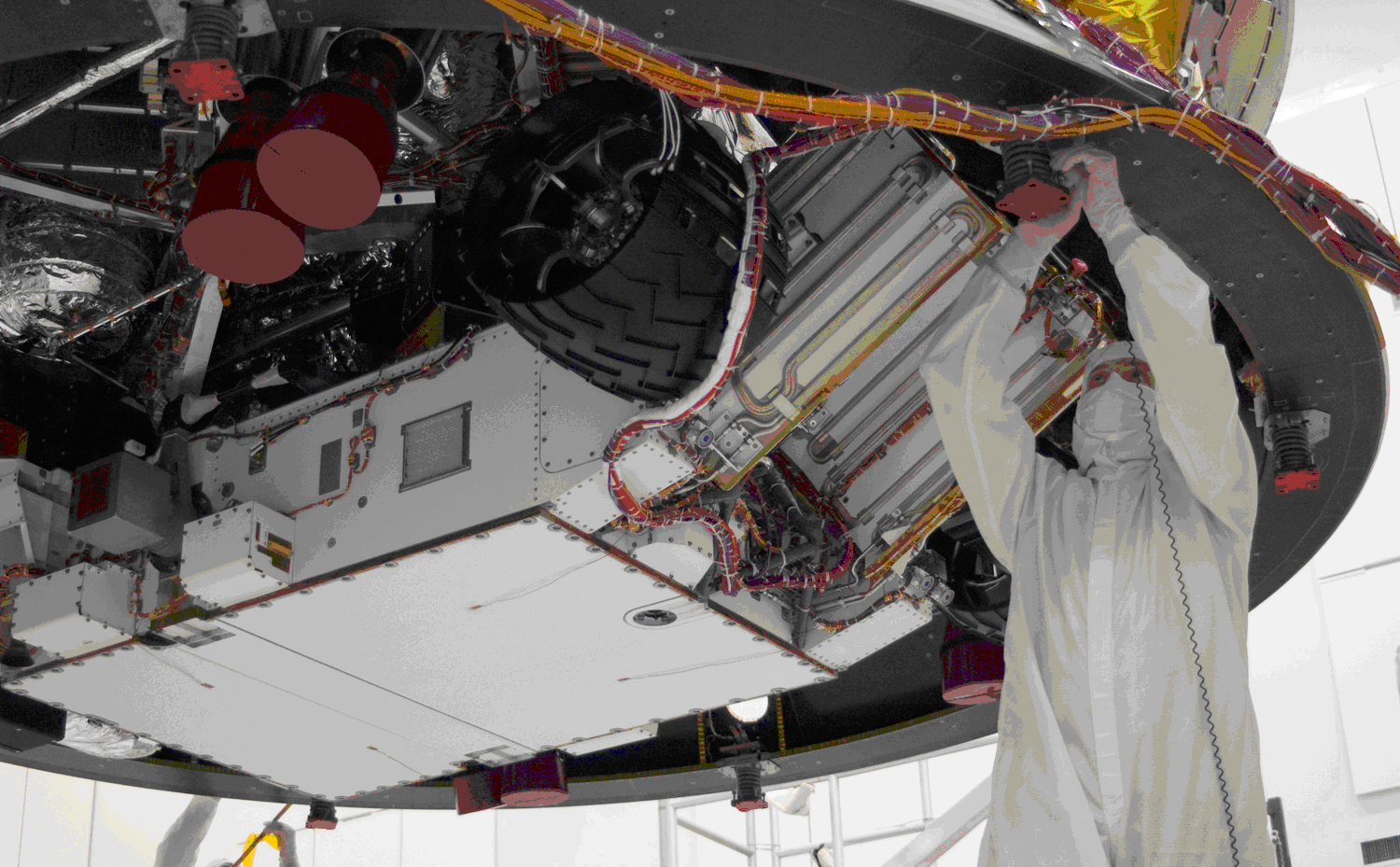 This image shows an engineer dressed in cleanroom coverall working on the rover which is overhead.