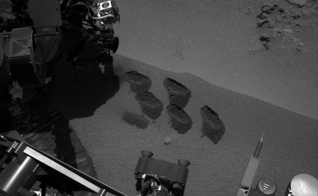 "NASA's Mars rover Curiosity used a mechanism on its robotic arm to dig up five scoopfuls of material from a patch of dusty sand called ""Rocknest,"" producing the five bite-mark pits visible in this image from the rover's left Navigation Camera (Navcam)."