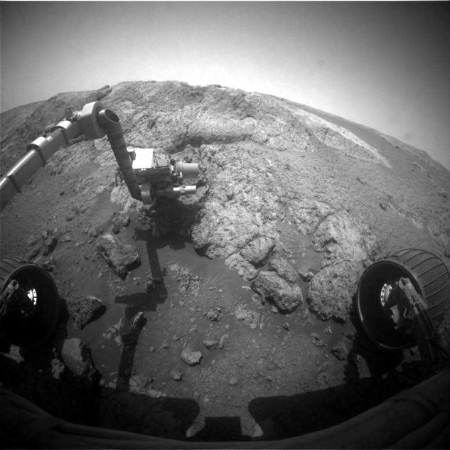 "This image from the front hazard-avoidance camera (Hazcam) on the NASA Mars Exploration Rover Opportunity shows the rover's arm extended for examination of a target called ""Onaping"" at the base of an outcrop called ""Copper Cliff"" in the Matijevic Hill area of the west rim of Endeavour Crater."