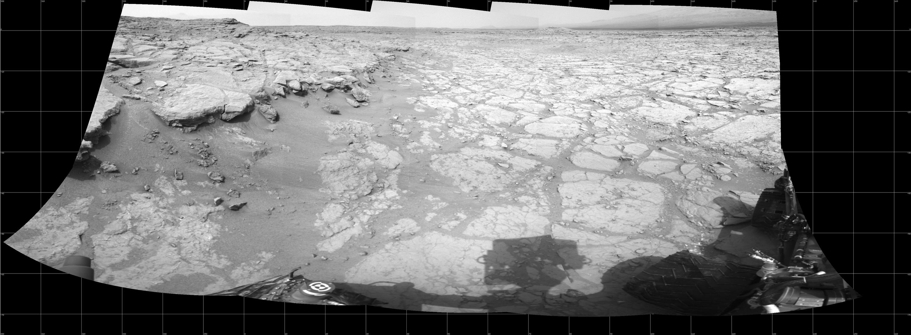 "In a shallow depression called ""Yellowknife Bay,"" the NASA Mars rover Curiosity drove to an edge of the feature during the 130th Martian day, or sol, of the mission (Dec. 17, 2012) and used its Navigation Camera to record this view of the ledge at the margin and a view across the ""bay."""
