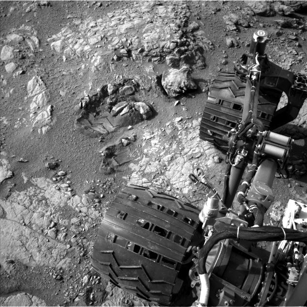"This view of Curiosity's left-front and left-center wheels and of marks made by wheels on the ground in the ""Yellowknife Bay"" area comes from one of six cameras used on Mars for the first time more than six months after the rover landed."