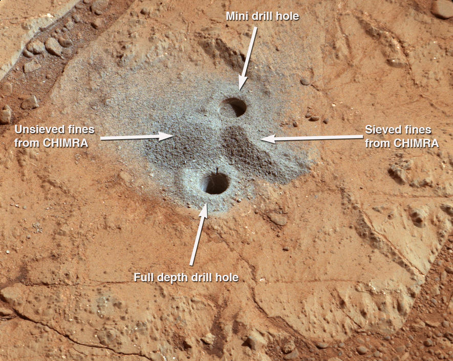 This image shows the first holes into rock drilled by NASA's Mars rover Curiosity, with drill tailings around the holes plus piles of powdered rock collected from the deeper hole and later discarded after other portions of the sample had been delivered to analytical instruments inside the rover.