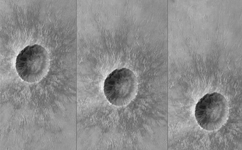 This black-and-white image shows a large crater and small crater on the surface of Mars in three views, in which the craters are in slightly different positions relative to the middle of each of the three frames. It simulates what the camera might see as it moved horizontally through the atmosphere during descent.  A sunflower-petal-like blanket of ejected rocks and soil surround the dark hole of the bright rimmed crater.