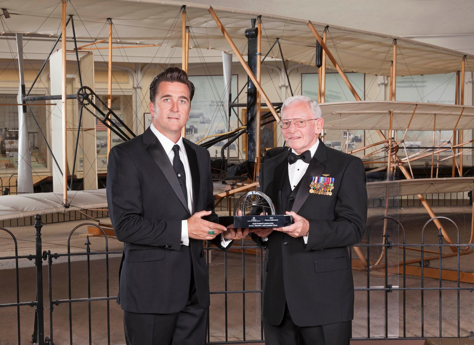 "The leader of the entry, descent and landing team of NASA's Mars Science Laboratory project, Adam Steltzner of JPL (left), accepts the 2013 Trophy for Current Achievement from the Smithsonian National Air and Space Museum from museum director Gen. J. R. ""Jack"" Dailey on April 24, 2013."