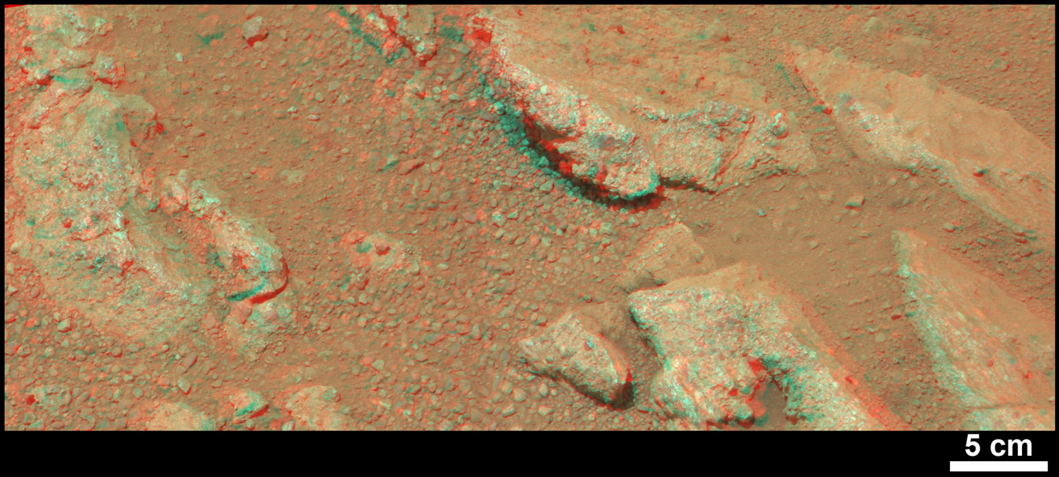 "This stereo view from NASA's Mars rover Curiosity shows a rock called ""Link,"" which bears rounded pebbles that provide evidence about vigorous flow of water in a stream on ancient Mars."