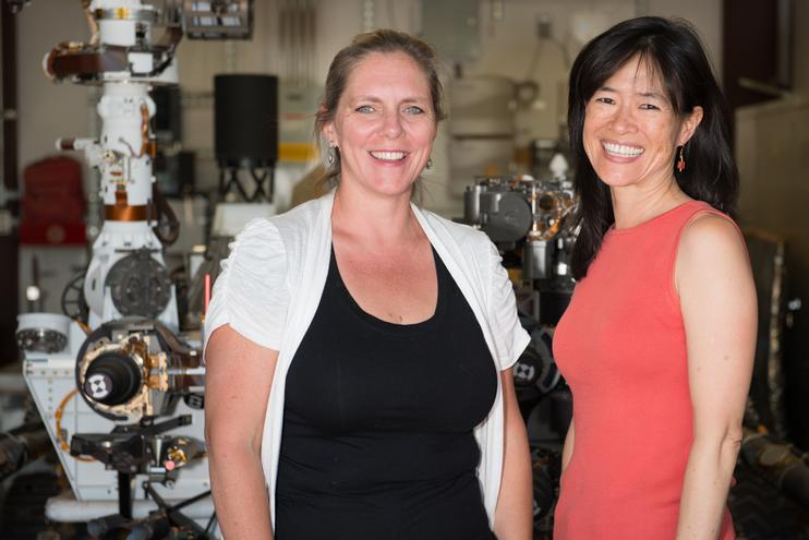 "Pictured here are Jennifer Trosper, MSL Deputy Project Manager and Grace Tan-Wang, Strategic Uplink Lead.  The image was taken in the ""Mars Yard"" where the ground test model of the Curiosity rover is housed."